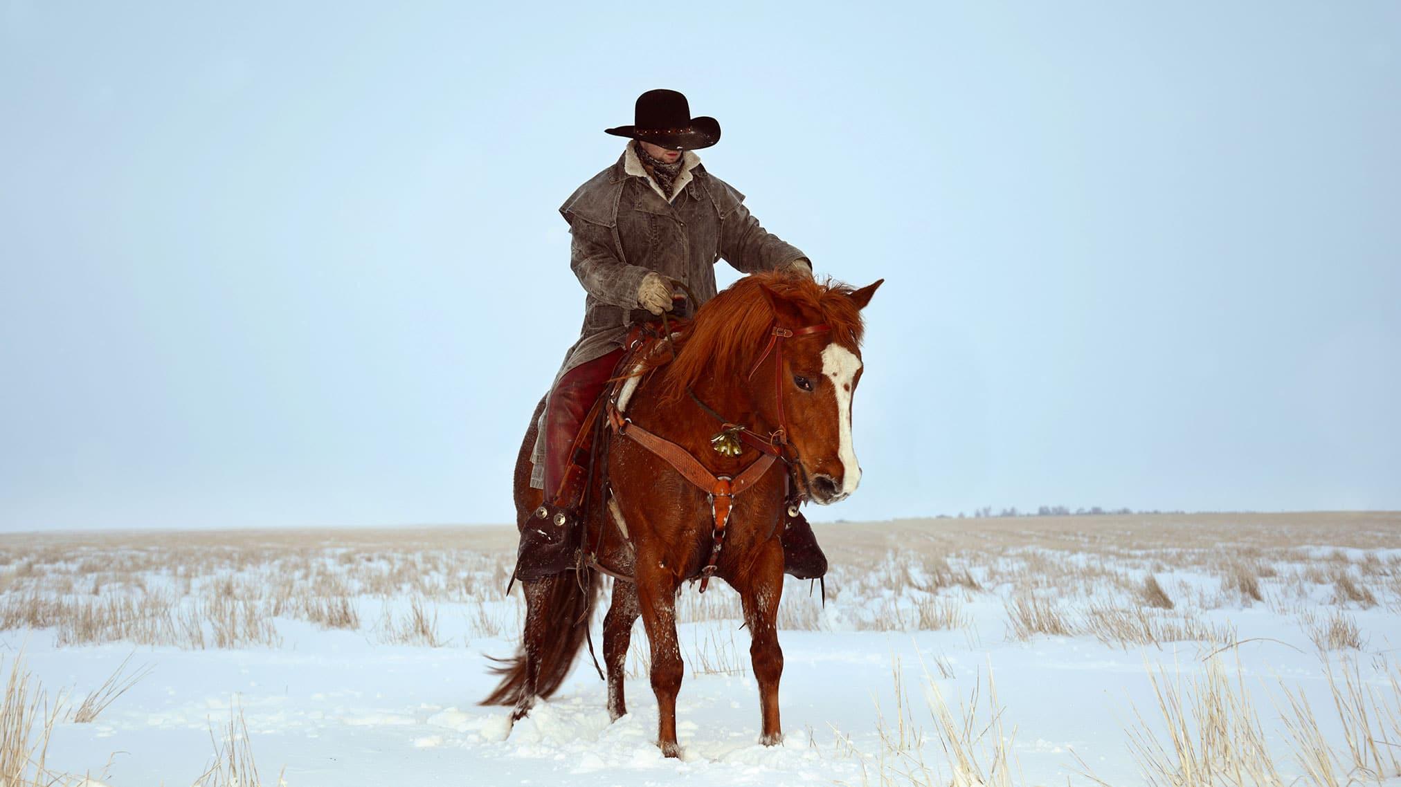 Cowboy op een paar in de sneeuw