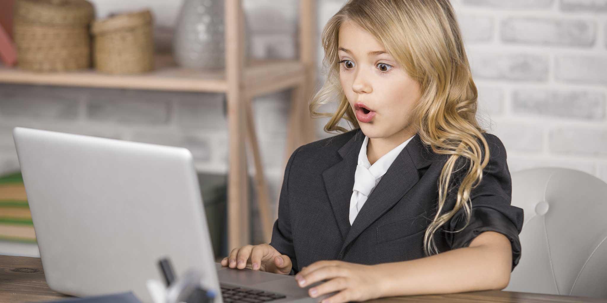 Klein meisje in pak met een laptop op een bureau
