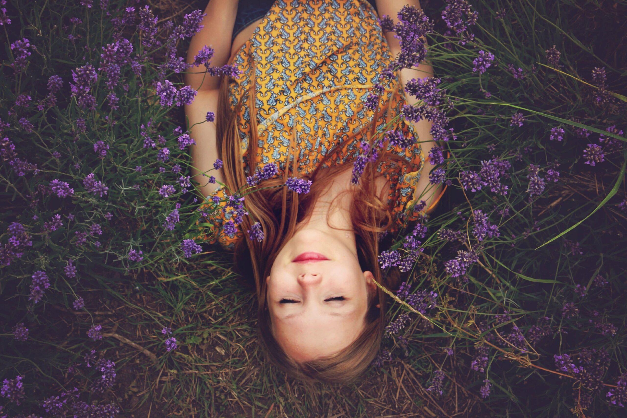 Jonge vrouw ligt in een wei met paarse bloemen