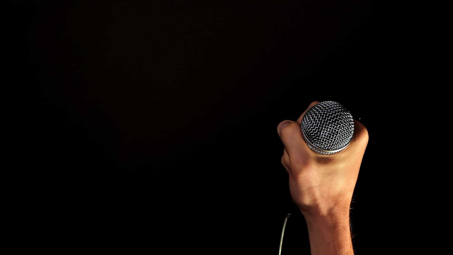 Een hand die een microphone vasthoudt
