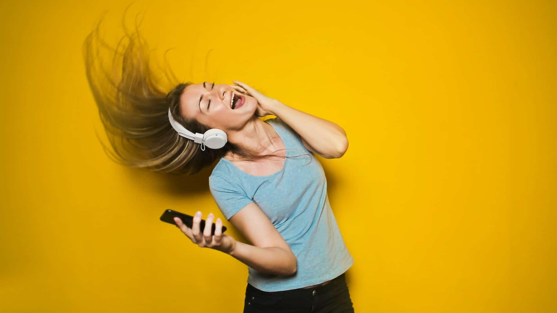 Blond/brunette blank meisje met een koptelefoon en een mobiel in de hand
