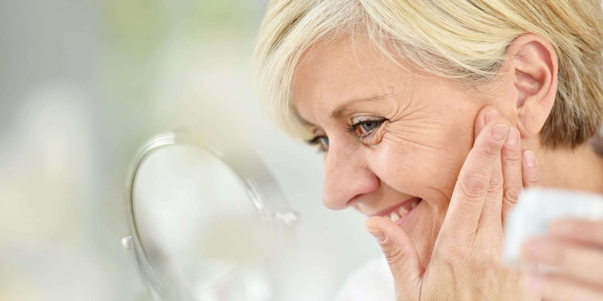 Middelbare vrouw bekijkt haarzelf in een spiegel