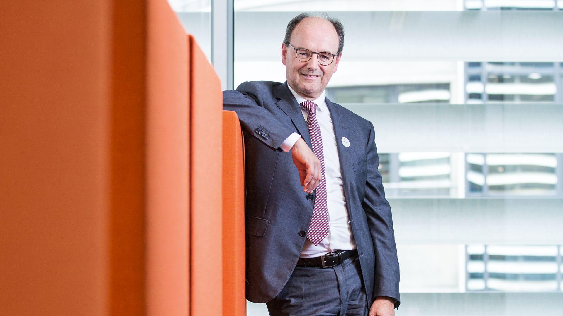 Jan Vander Stichele leunt met een arm op oranje blokken terwijl hij lachend kijkt naar de camera
