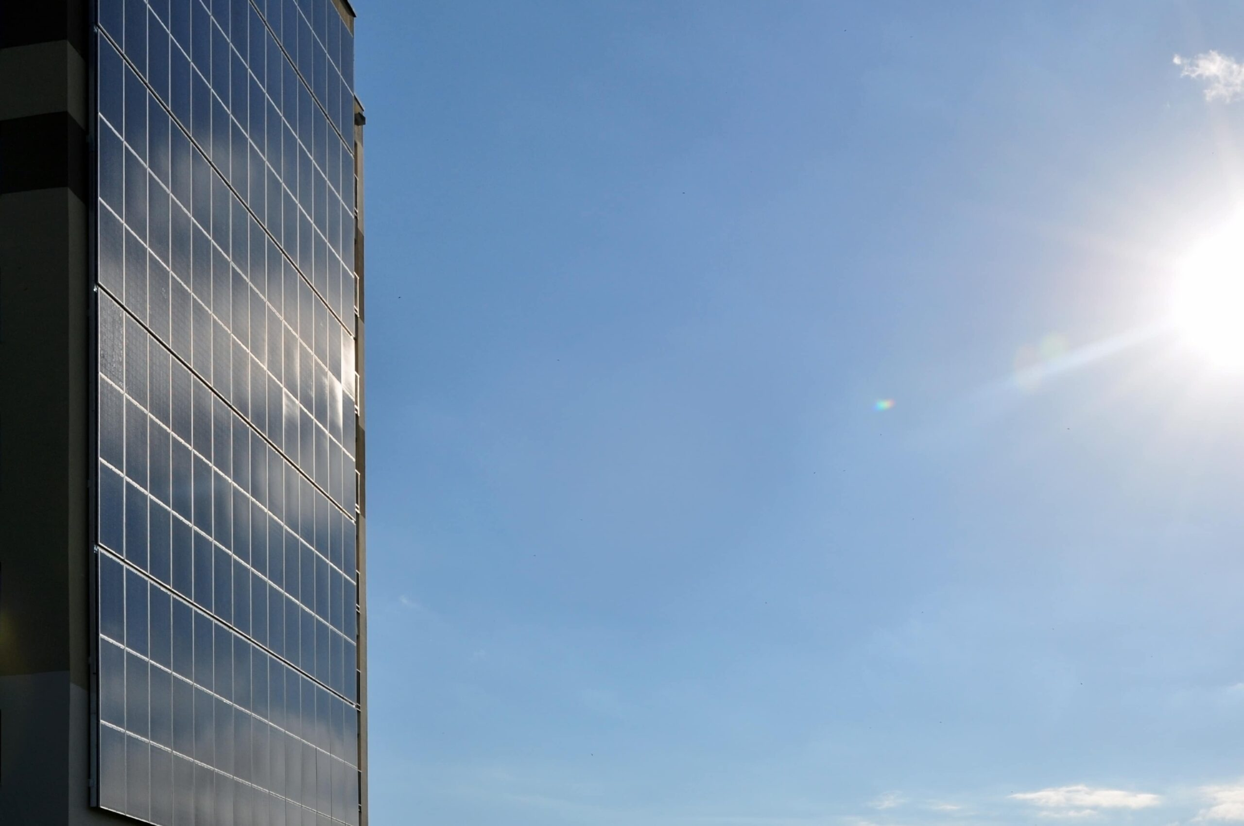 Wall with a wide solar panel against the blue sky. Empty space.