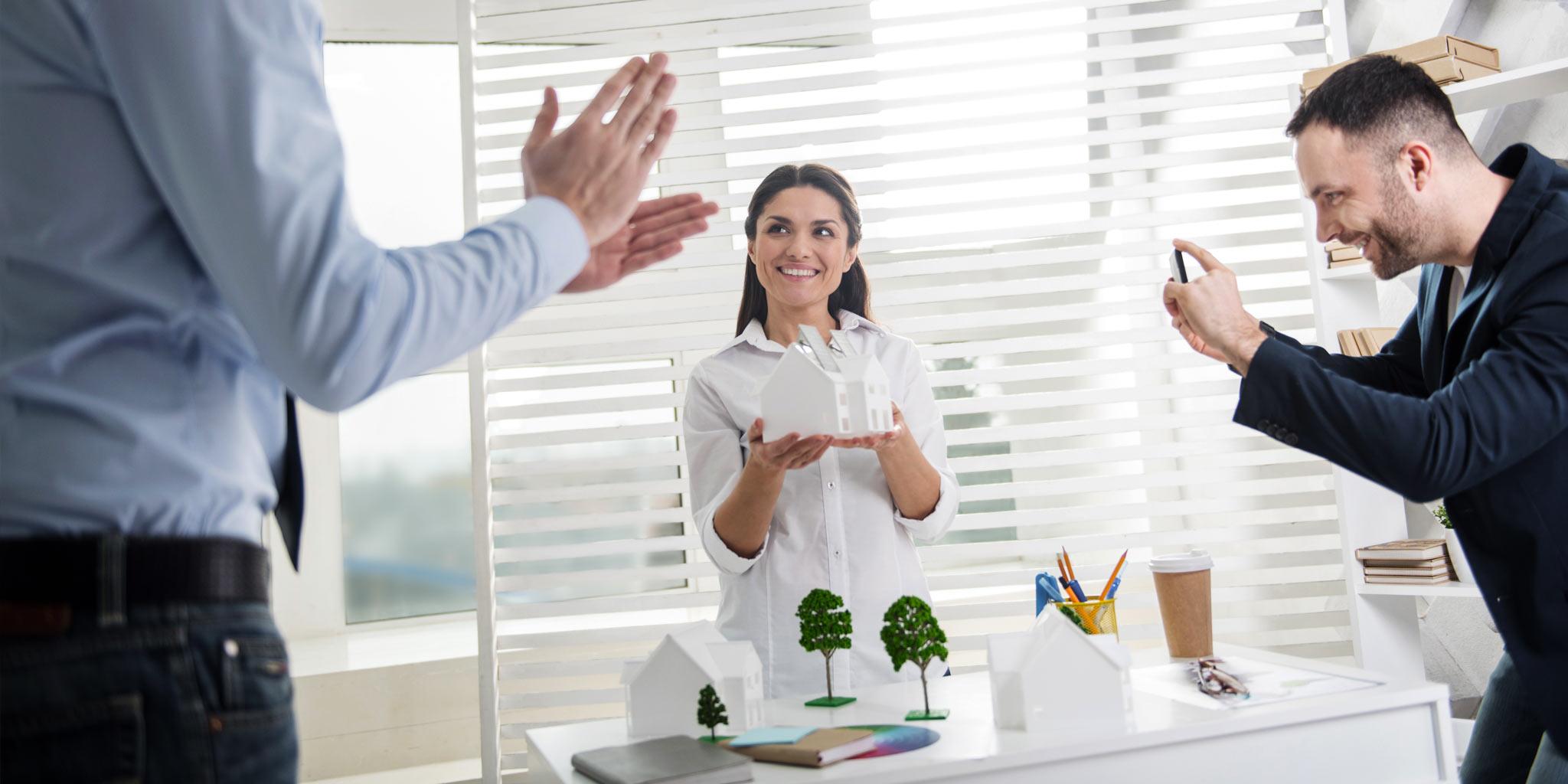 Vrouw heeft een miniatuur van een huis vast, één man trekt een foto en de andere klapt in zijn handen