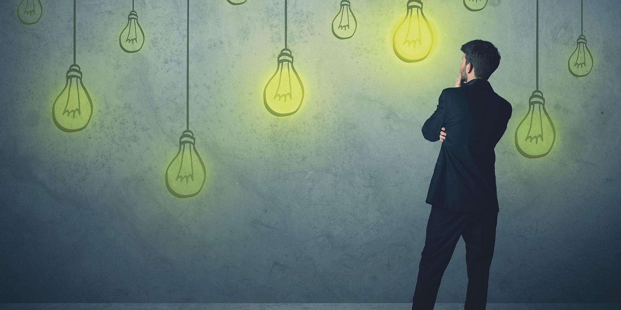 Homme en costume regardant un mur plein de lampes