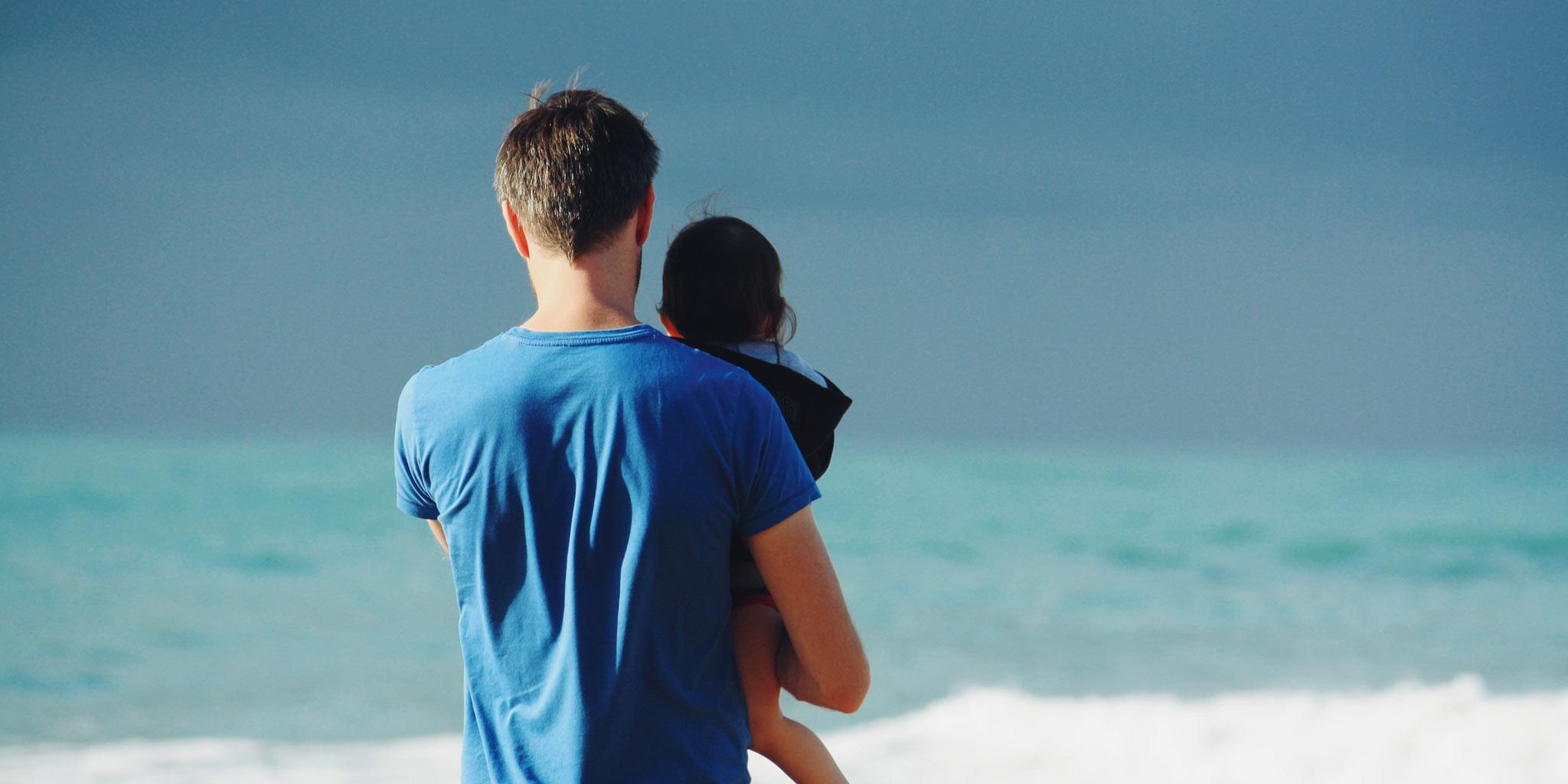 Man en kind staren naar de zee
