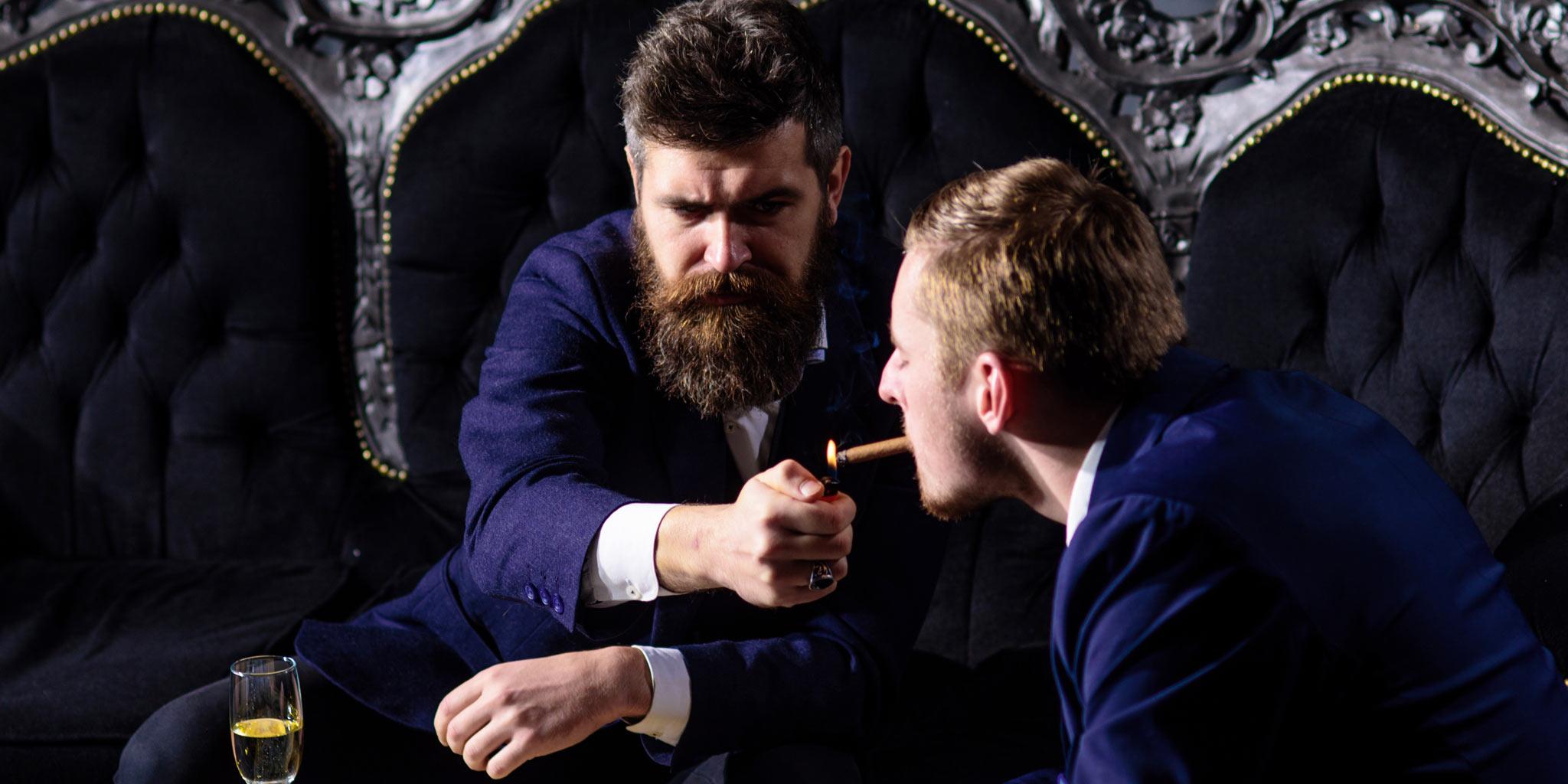 Een man die de sigaar van de andere man. aansteekt