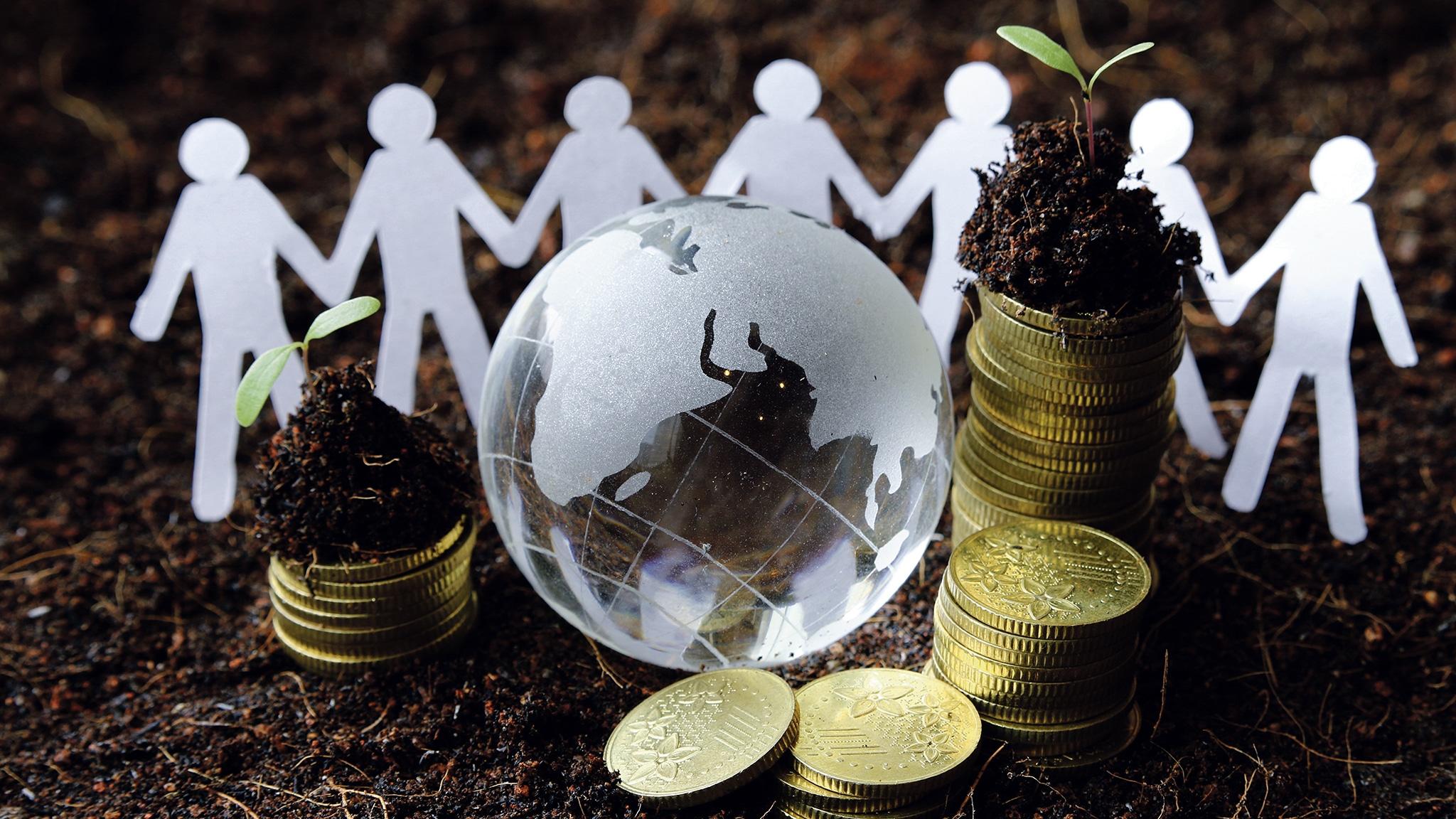 Papieren mannetjes rond munten en een glazen wereldbol op aarde