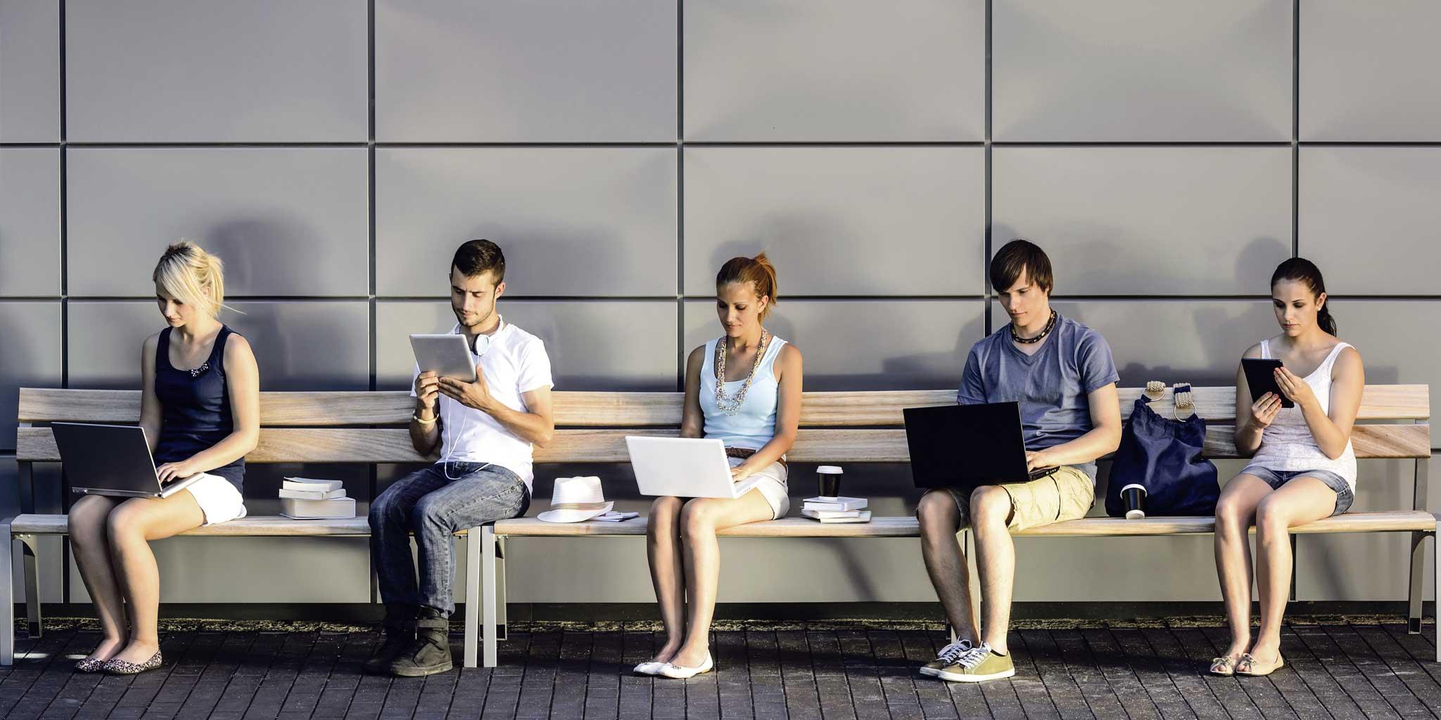 Vijf jongeren op een bankje met elk een elektronisch toestel in de hand