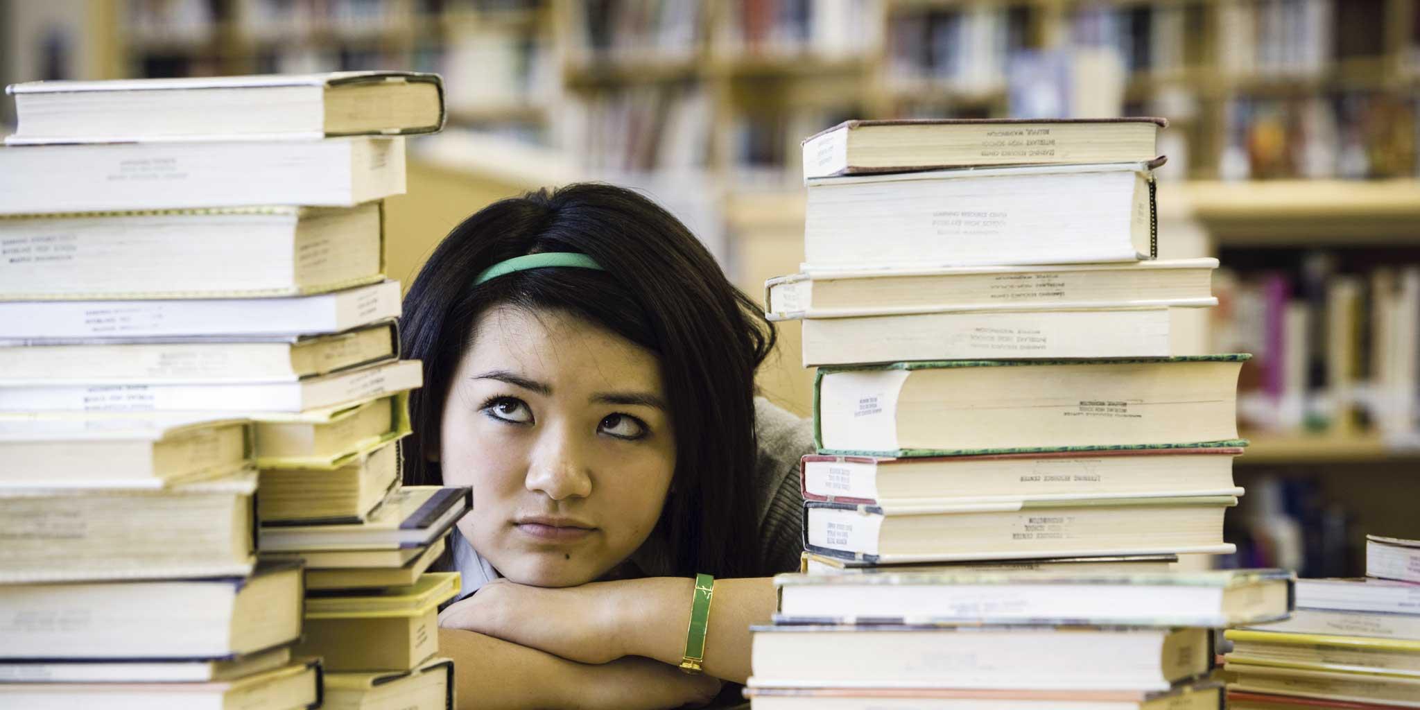 Jong meisje kijkend naar stapel boeken