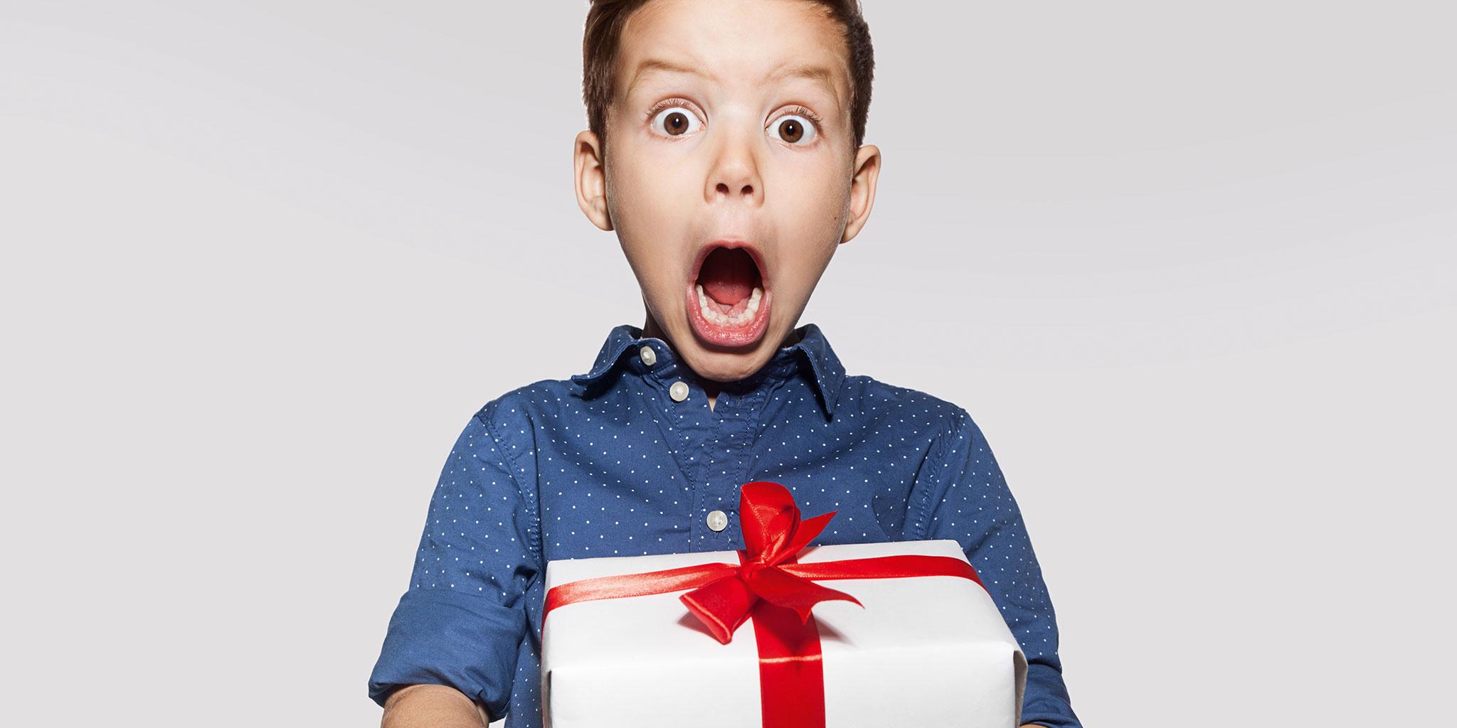 Garçon à bouche ouverte tenant un cadeau de Noël