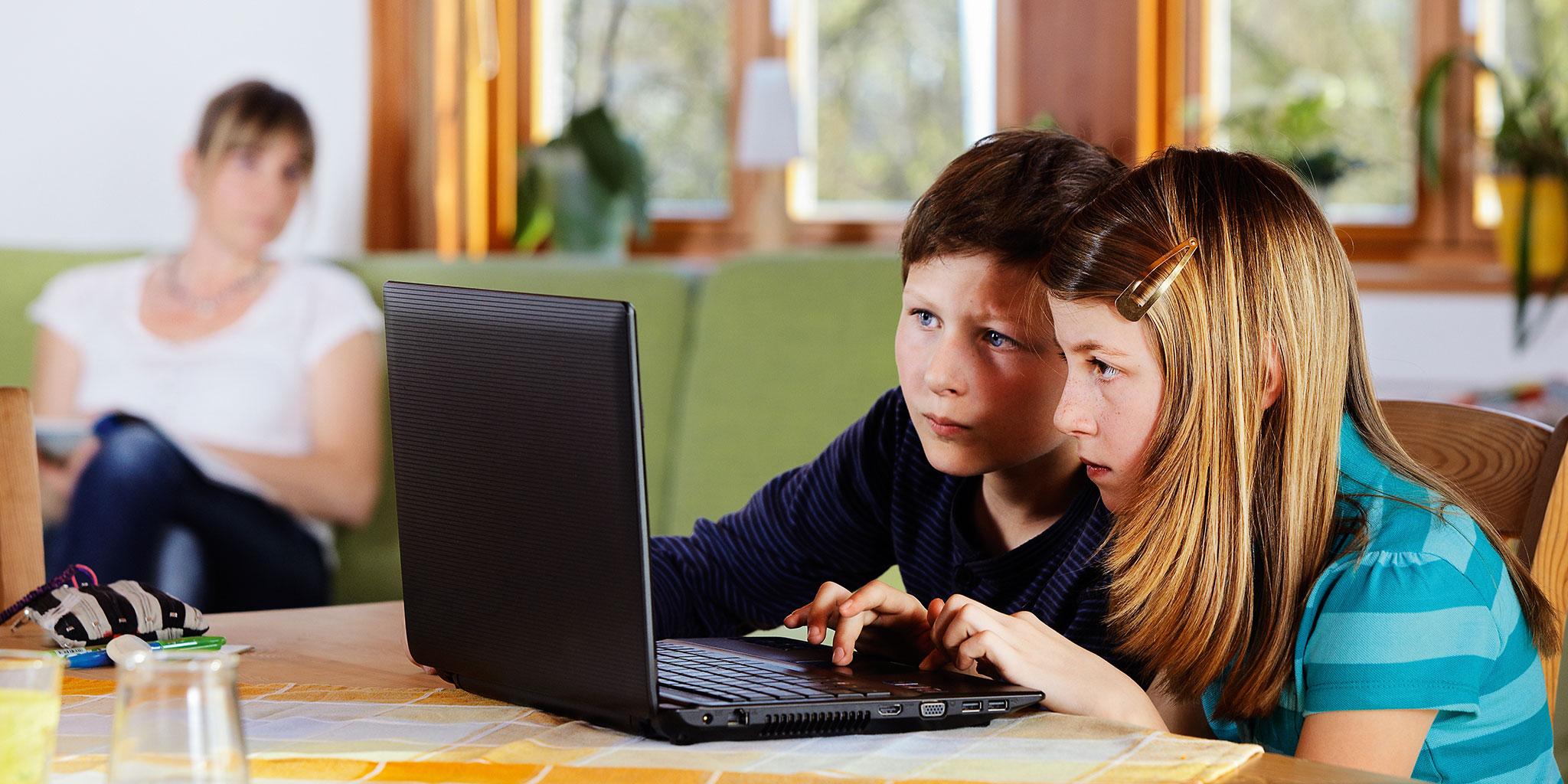 Deux enfants sur un ordinateur portable pendant que leur mère les regarde à l'arrière-plan.