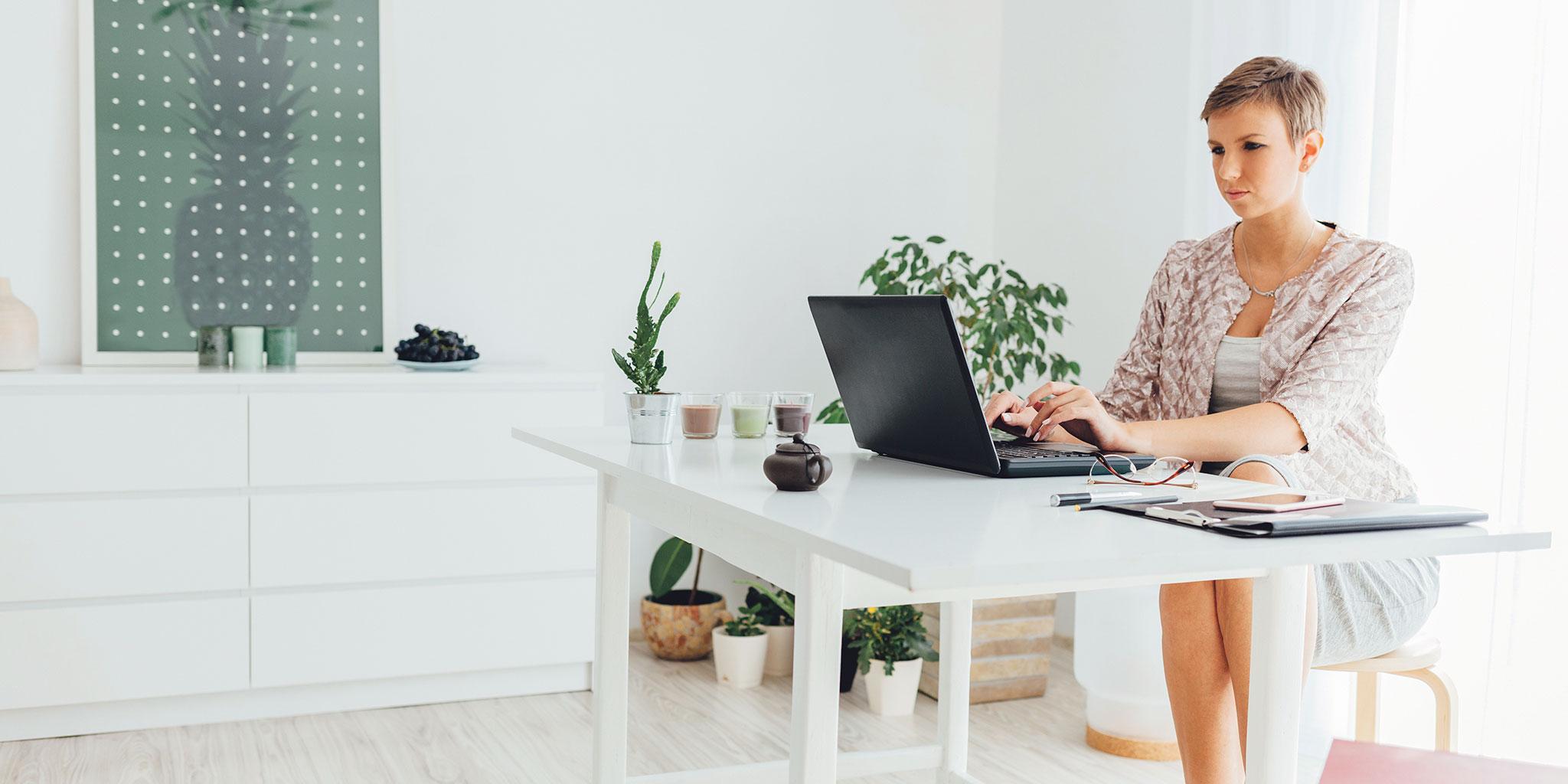 Femme avec les jambes croisées à un bureau occupé avec son ordinateur portable