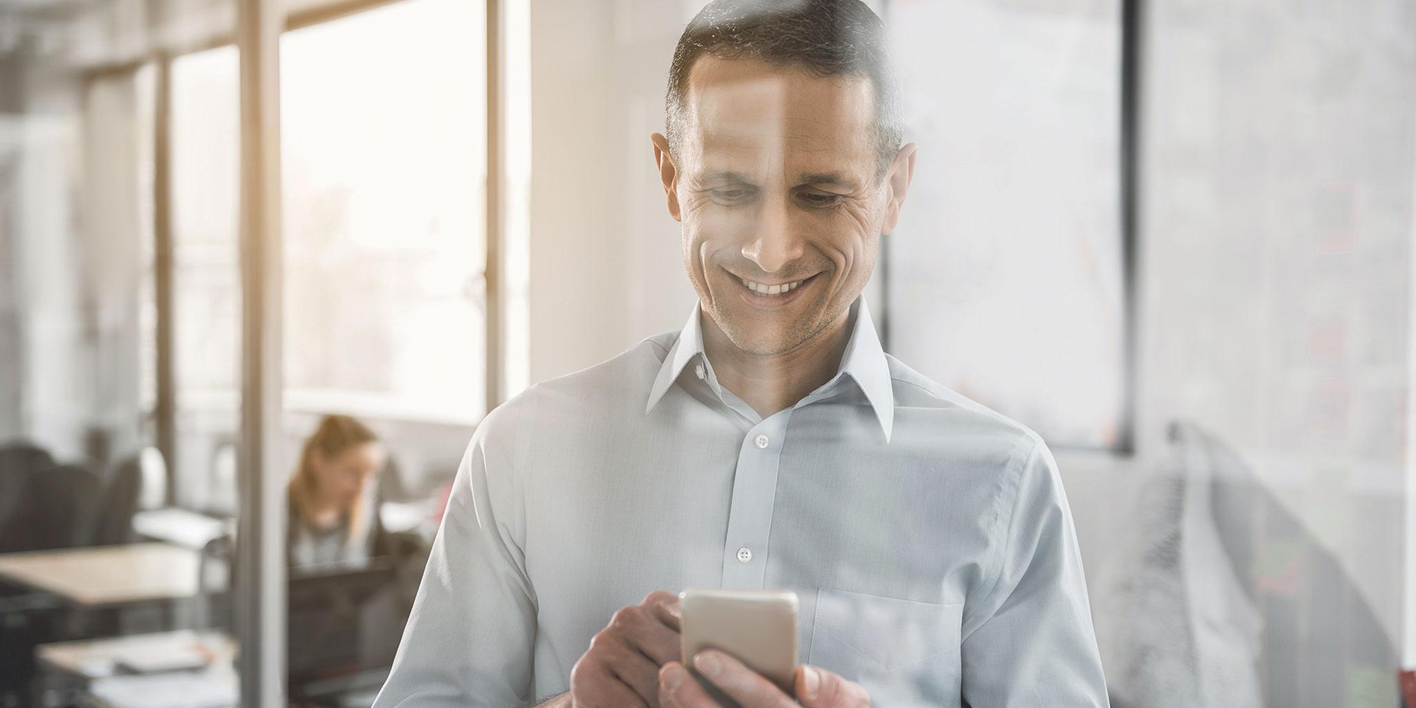 Un homme tape sur son smartphone en riant