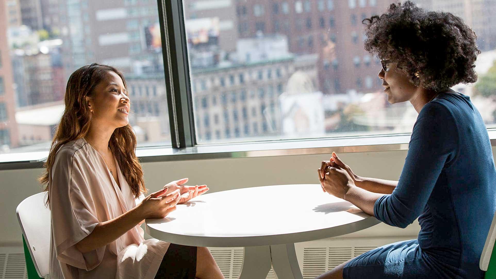 Twee vrouwen aan een ronde tafel die een conversatie aan het voeren zijn.