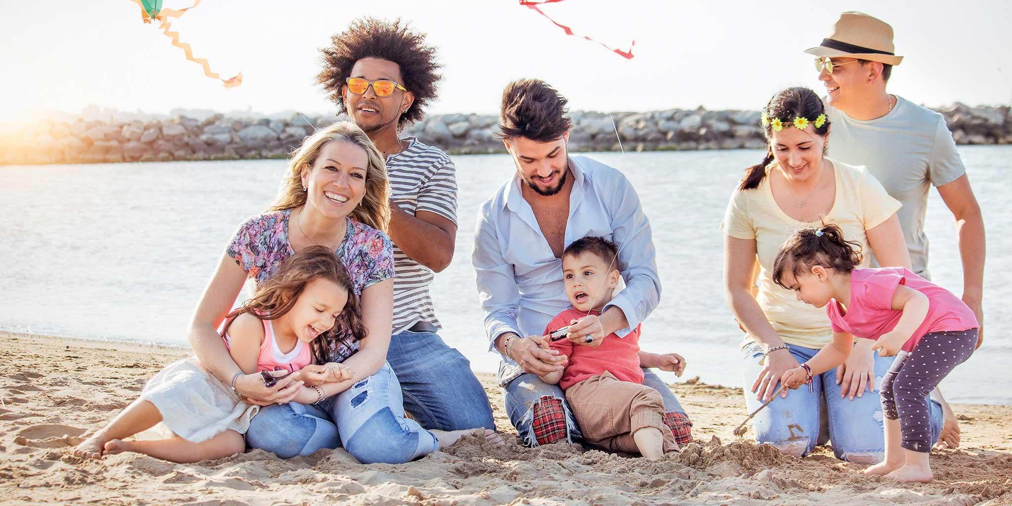 Verschillende gezinnen op het strand met hun kinderen