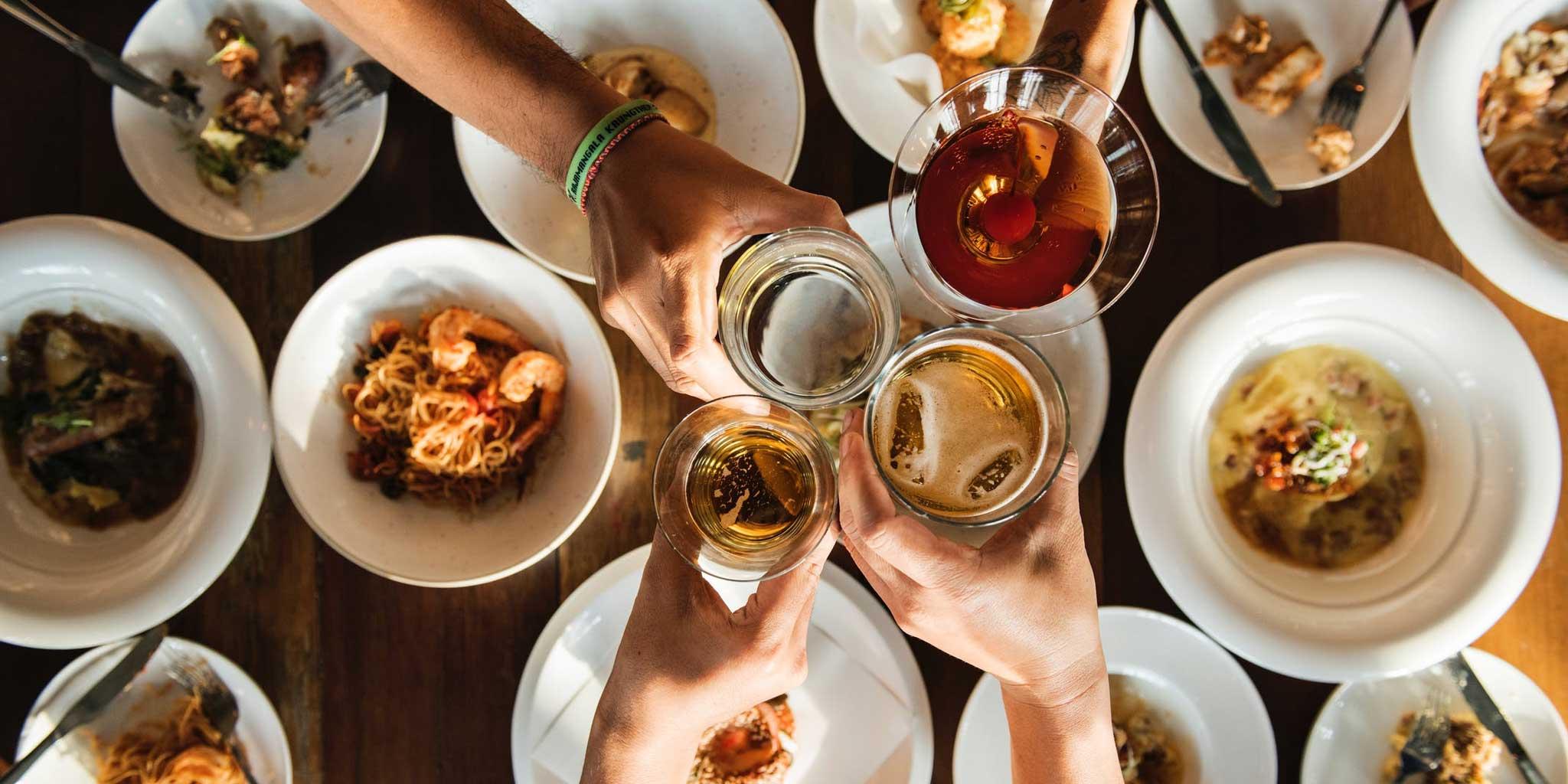 Handen met glazen en verschillende gerechten op de achtergrond