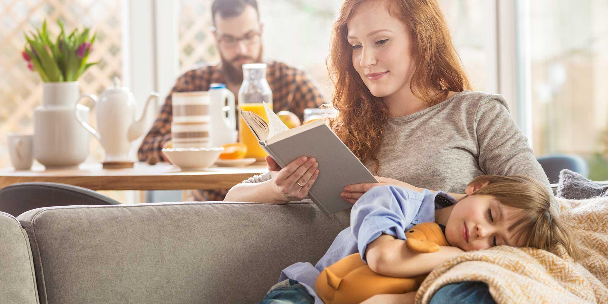 FokusMijnGezin-MeTime- Mama die een boek leest terwijl haar zoon op haar schoot ligt en op de achtergrond is er een man aan tafel