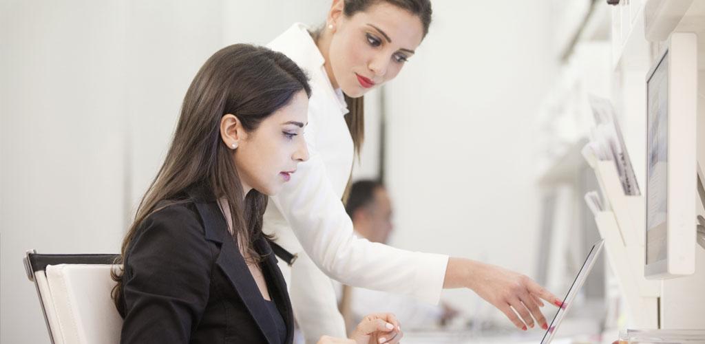 Deux femmes en costumes, l'une assise à un bureau et l'autre pointée vers un écran.