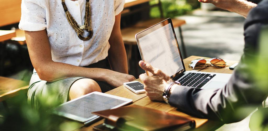 Homme et femme à un bureau. Sur le bureau se trouvent un téléphone portable, des lunettes de soleil, un ordinateur portable et un agenda.