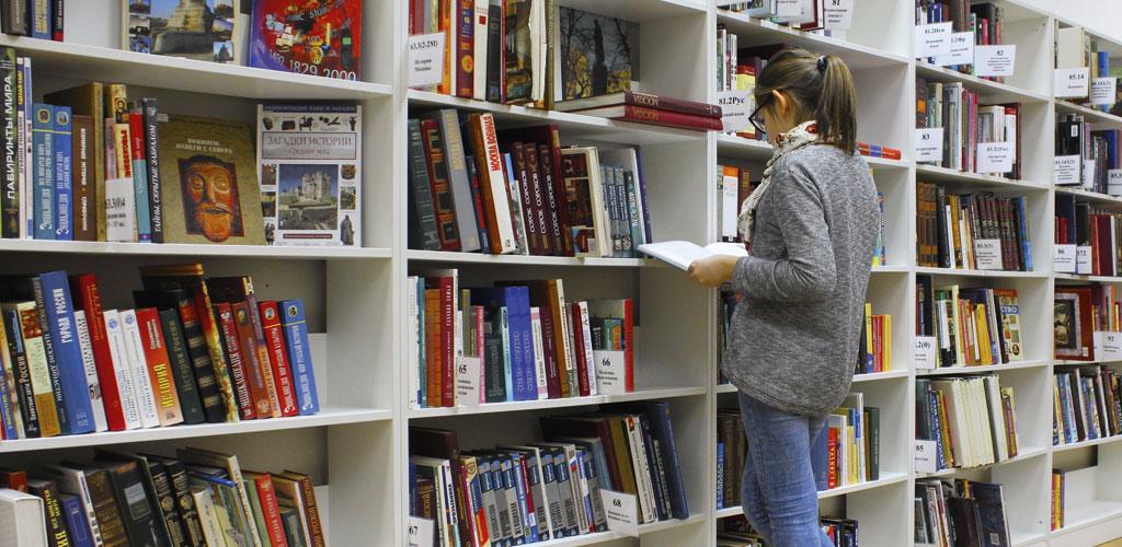 une femme avec un livre à la main dans la bibliothèque