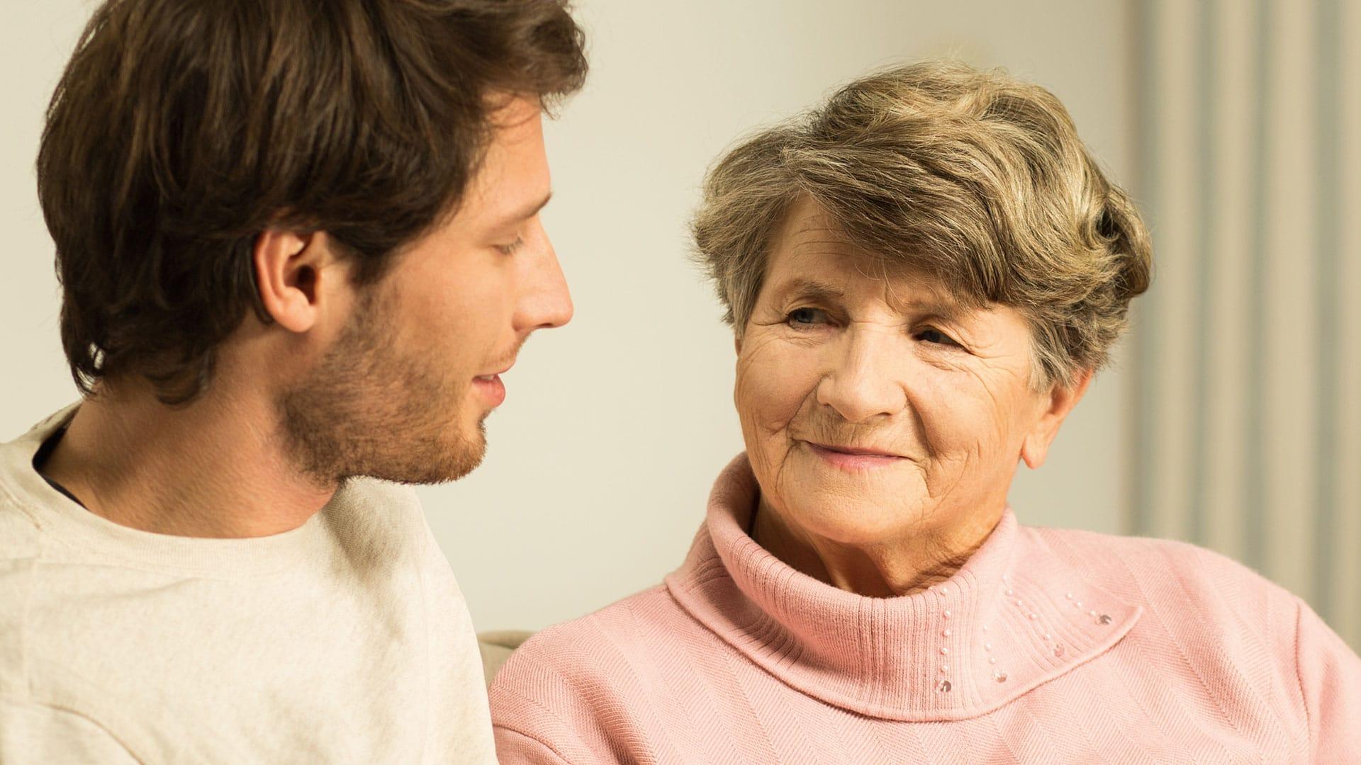Oudere vrouw en een man kijken naar elkaar lachend oog in oog