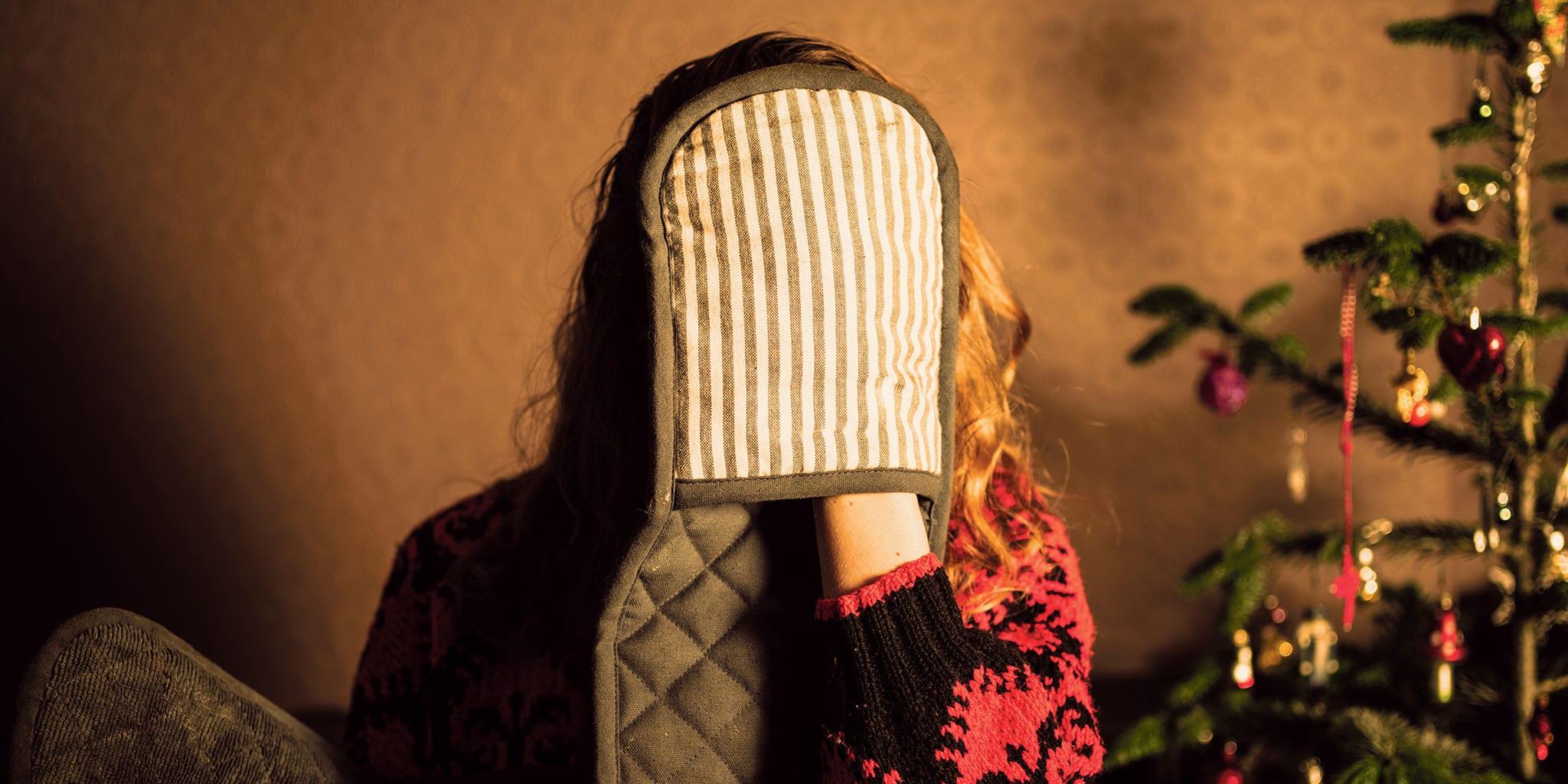 Vrouw met een ovenwant die haar gezicht bedekt