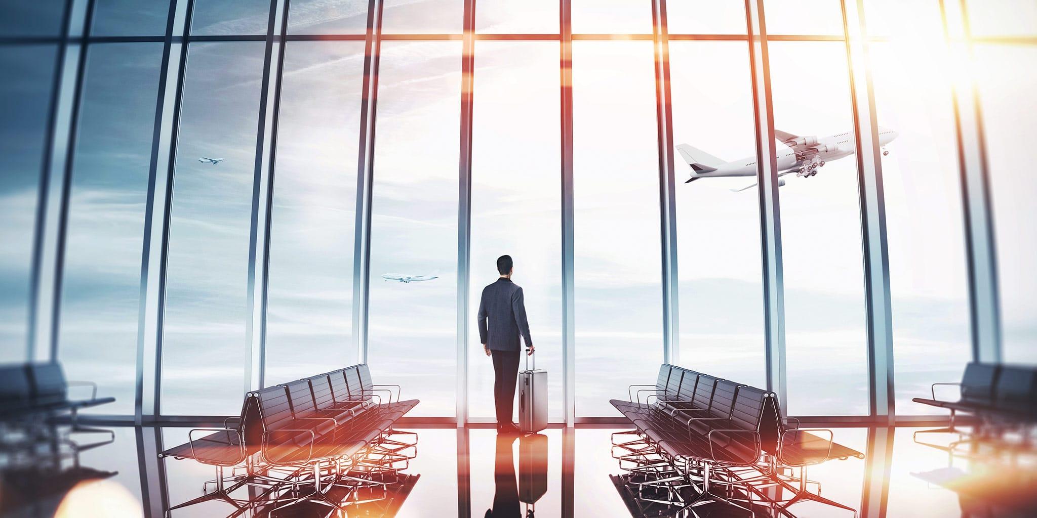 Man met een koffer kijkt naar de vliegtuigen in de lucht