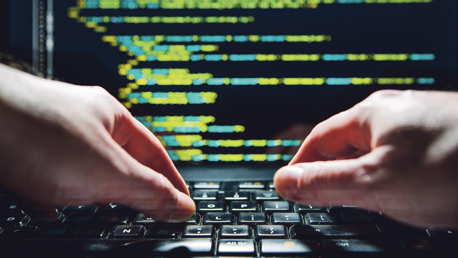 Iemand bezig op een pc met op de scherm een code