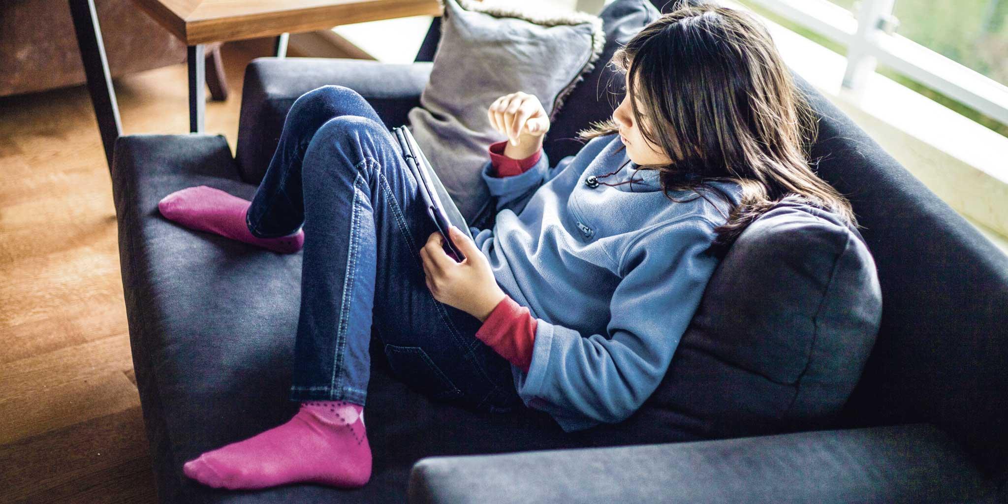 Kind zit in de zetel met een tablet op haar schoot