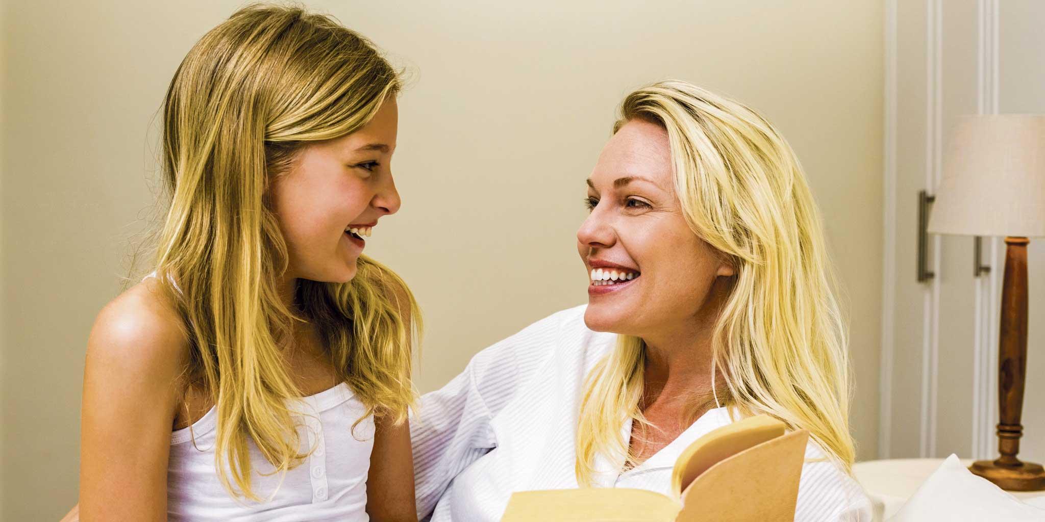 Blonde vrouw en kind kijken elkaar lachend aan