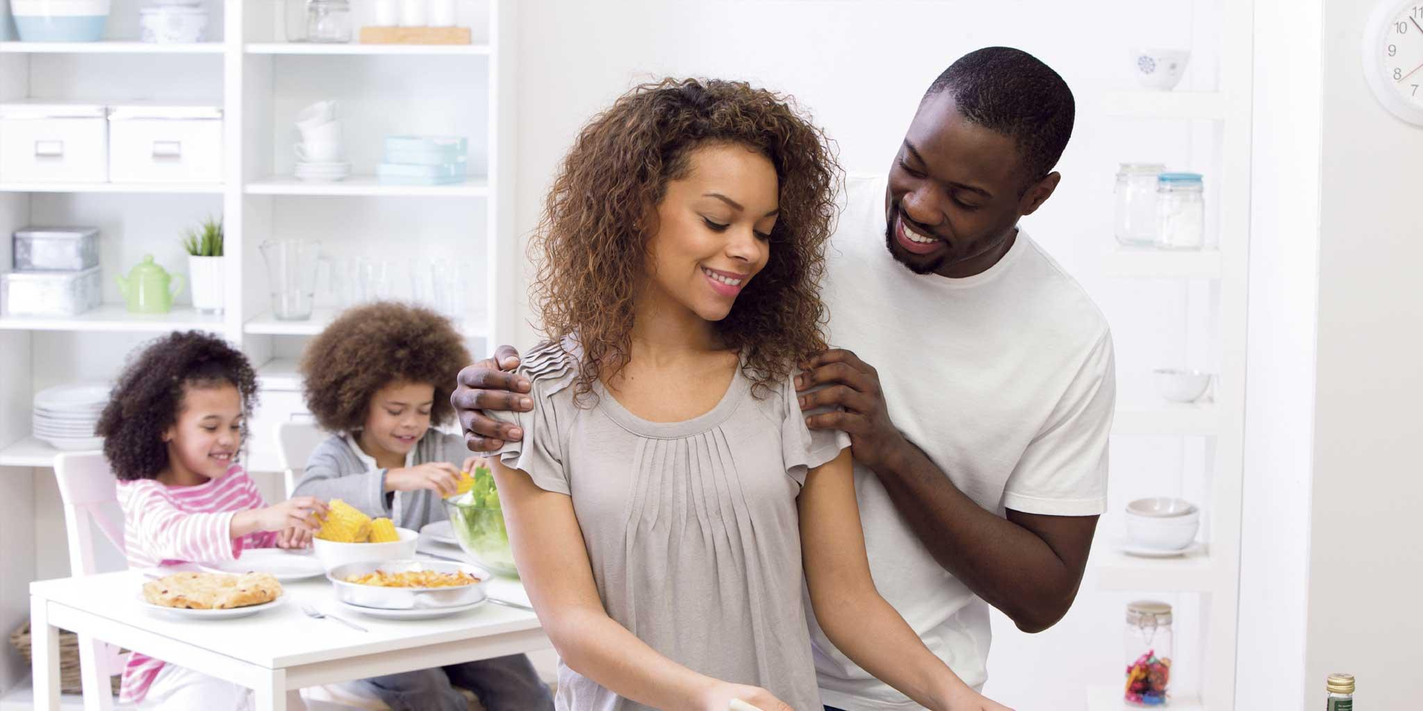 Zwarte man en vrouw lachen en op de achtergrond hun kinderen aan tafel met voedsel