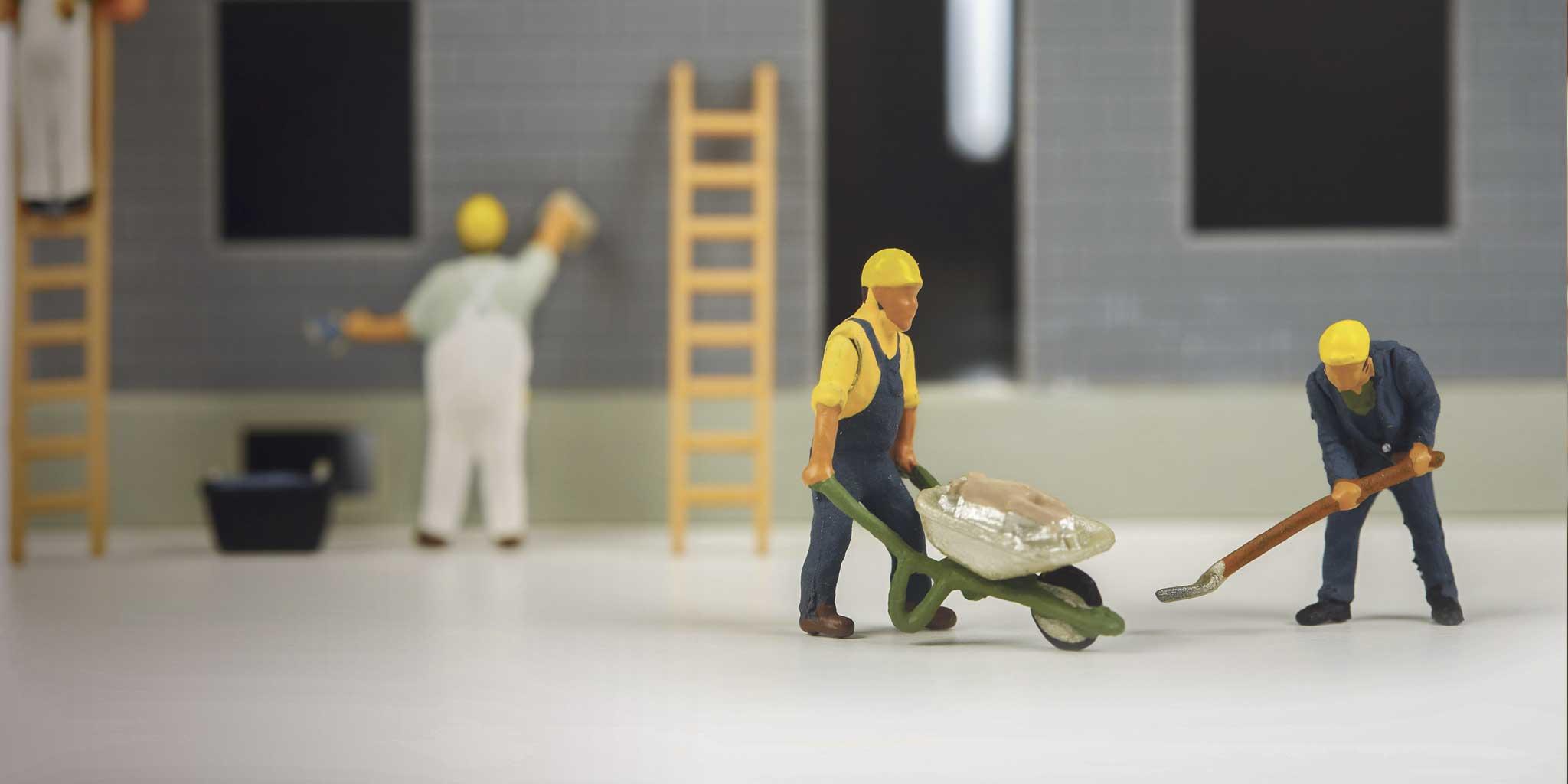 Kleine mannelijke poppen die bezig zijn met bouwen