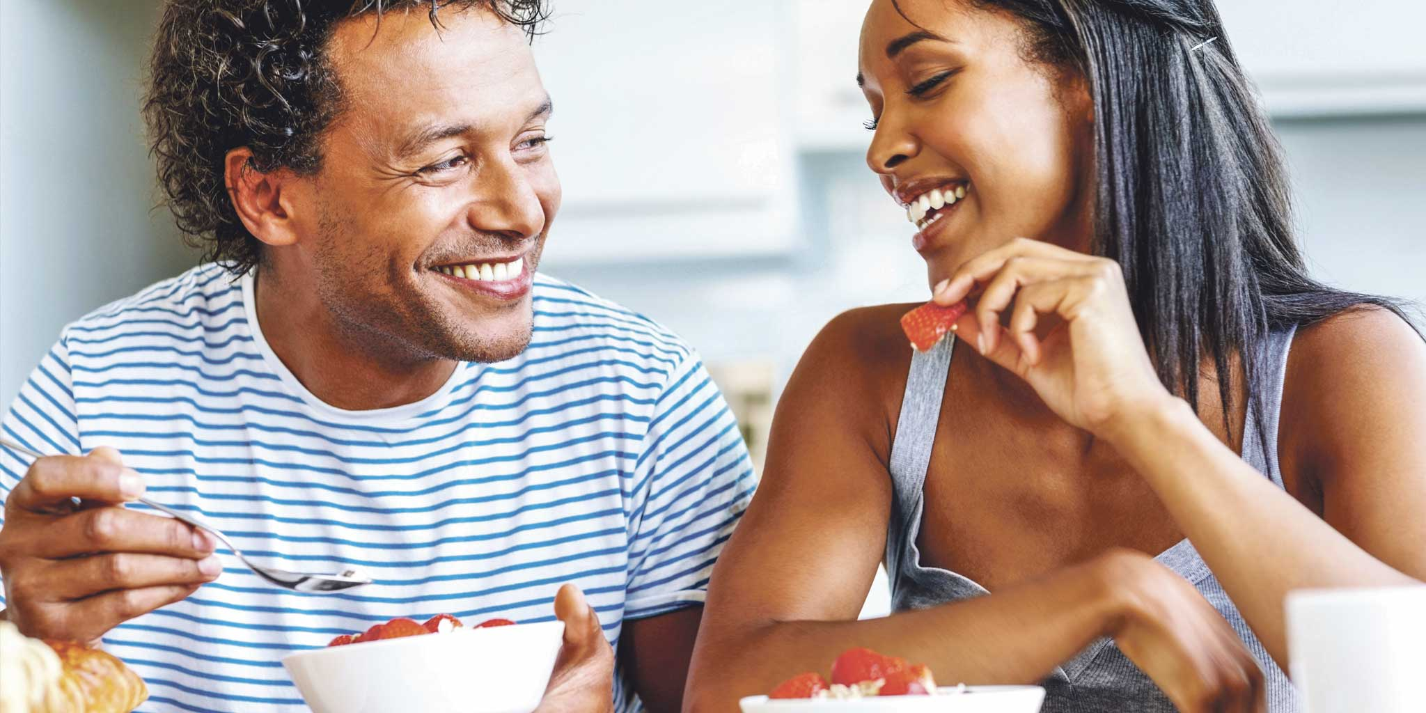 Lachende man en vrouw die genieten van gezonde voeding