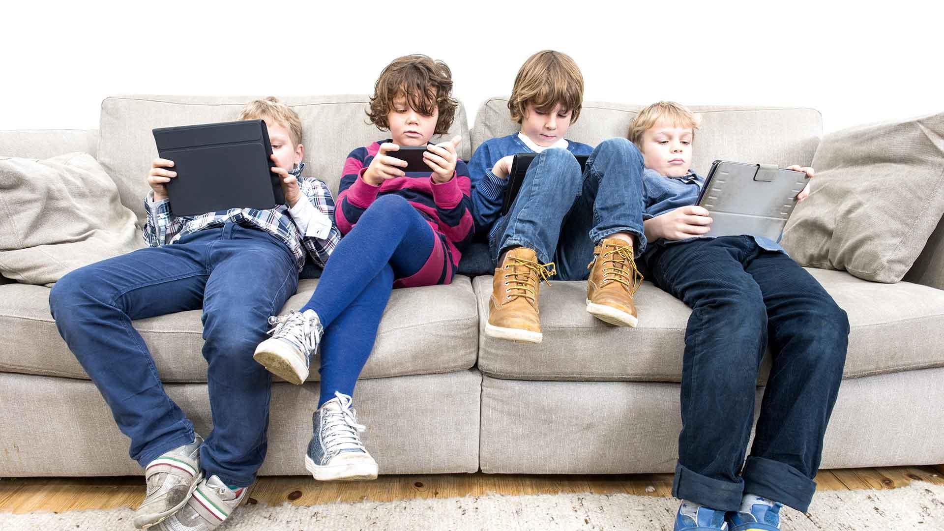 quatre enfants dans la chaise avec chacun une tablet à la main