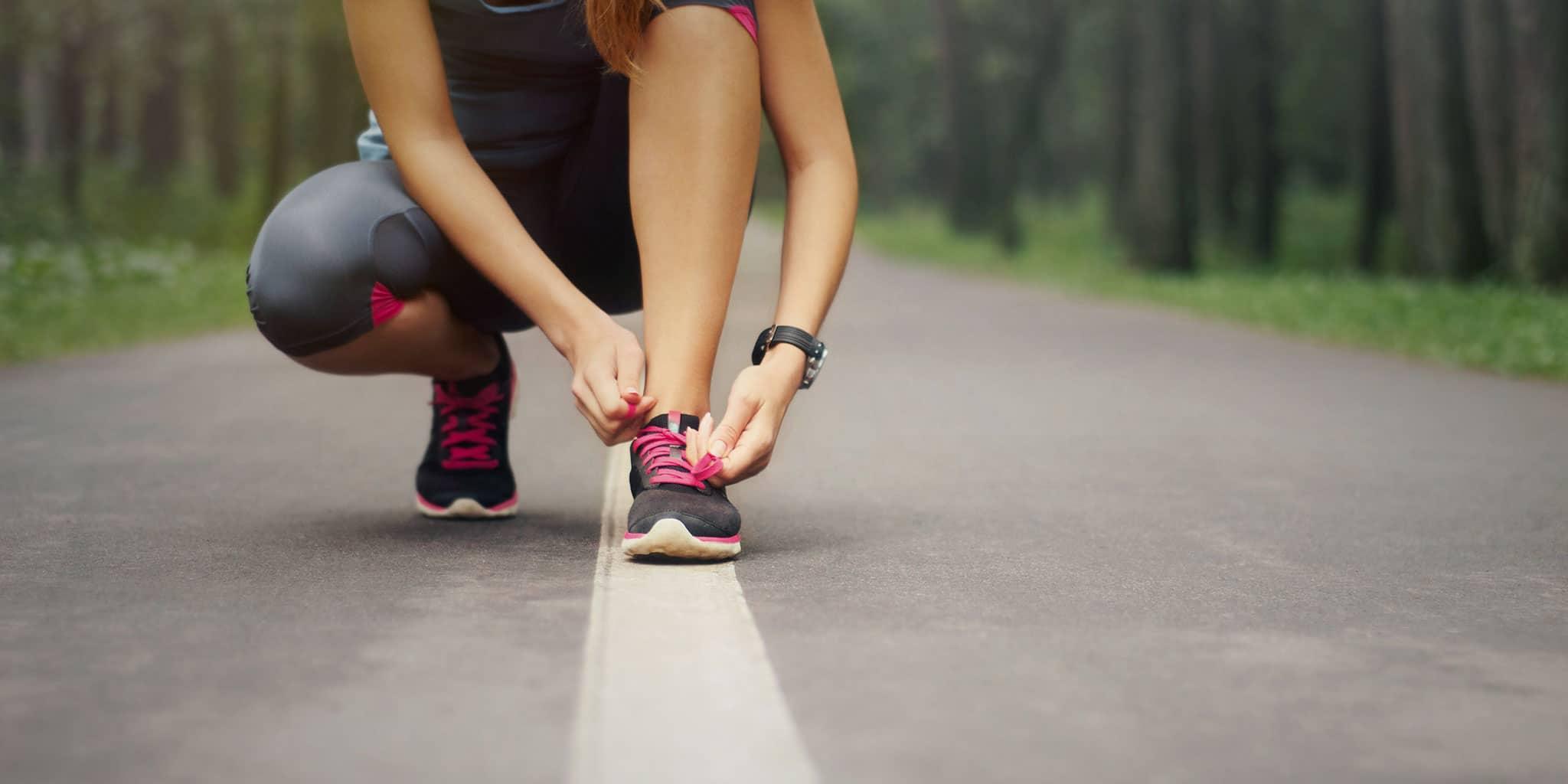 Vrouw die haar veter strikt om te gaan joggen