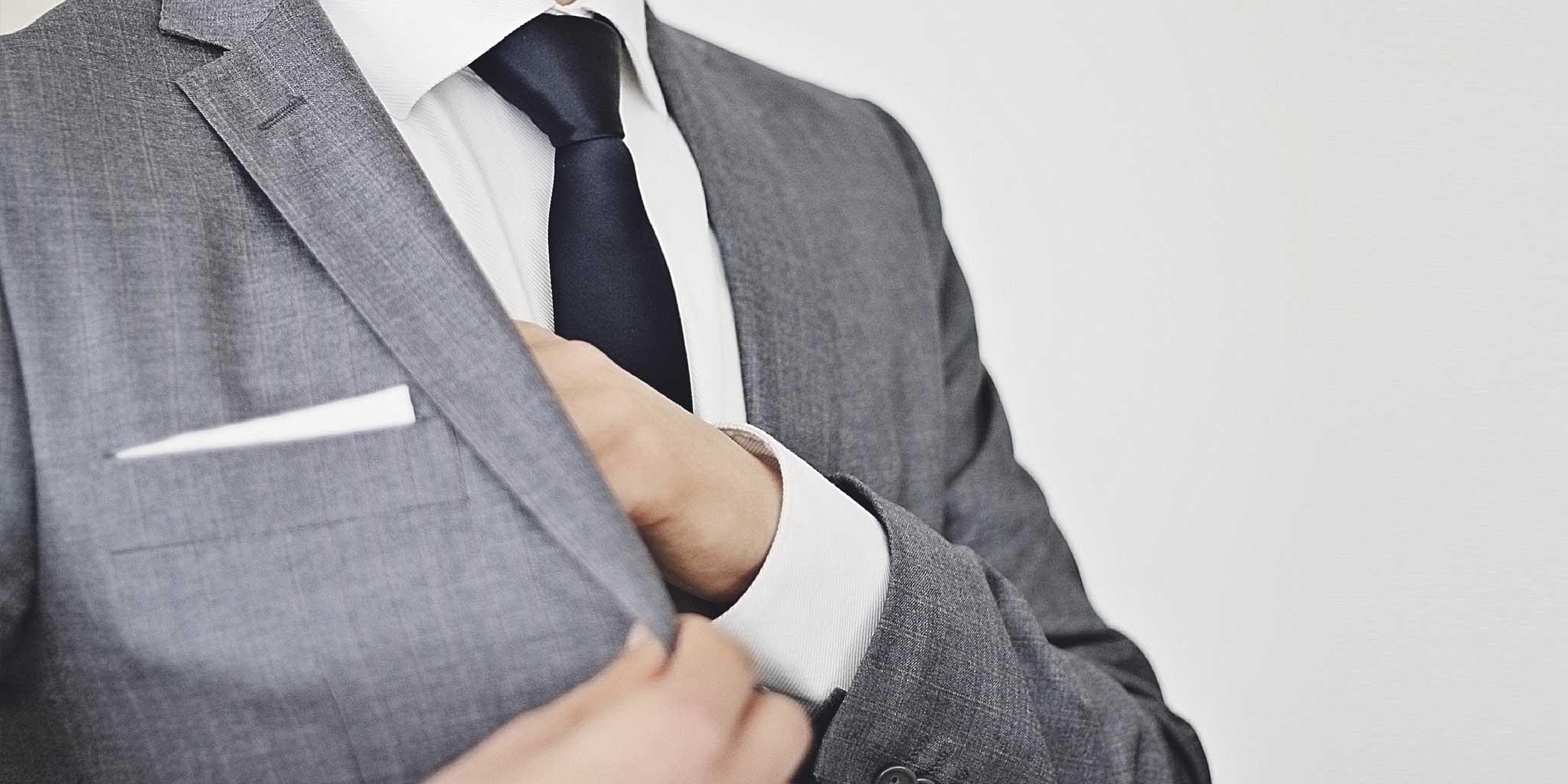 Man in pak met zijn hand in de zijzak