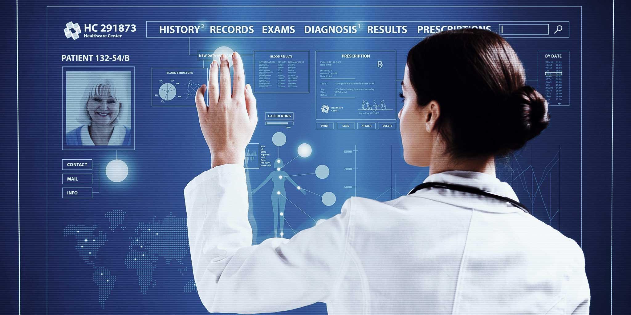 Vrouw in een labojas kijkend naar een scherm met patiëntengegevens