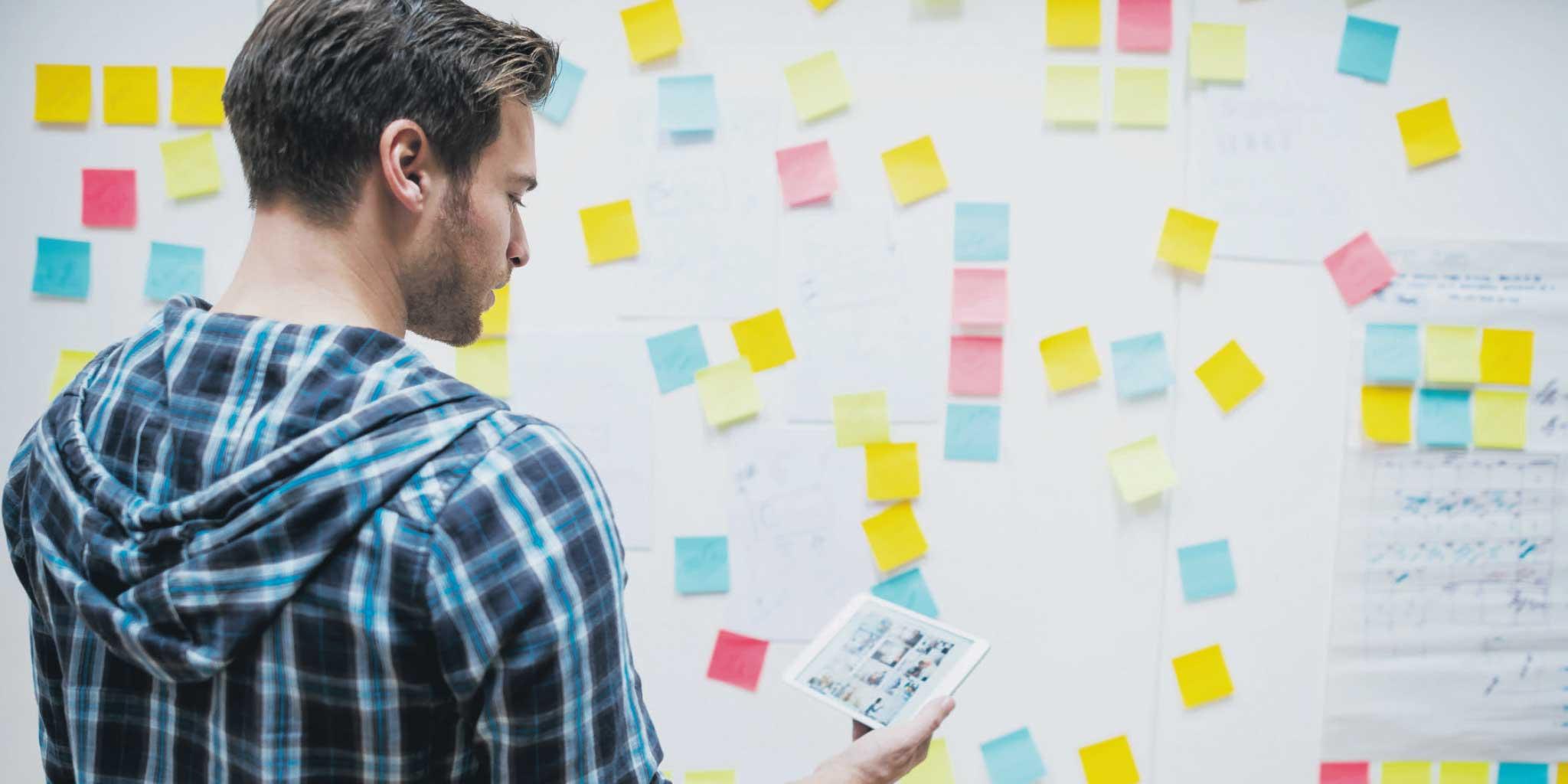Man met een tablet en post it notities geplakt op een grote papier