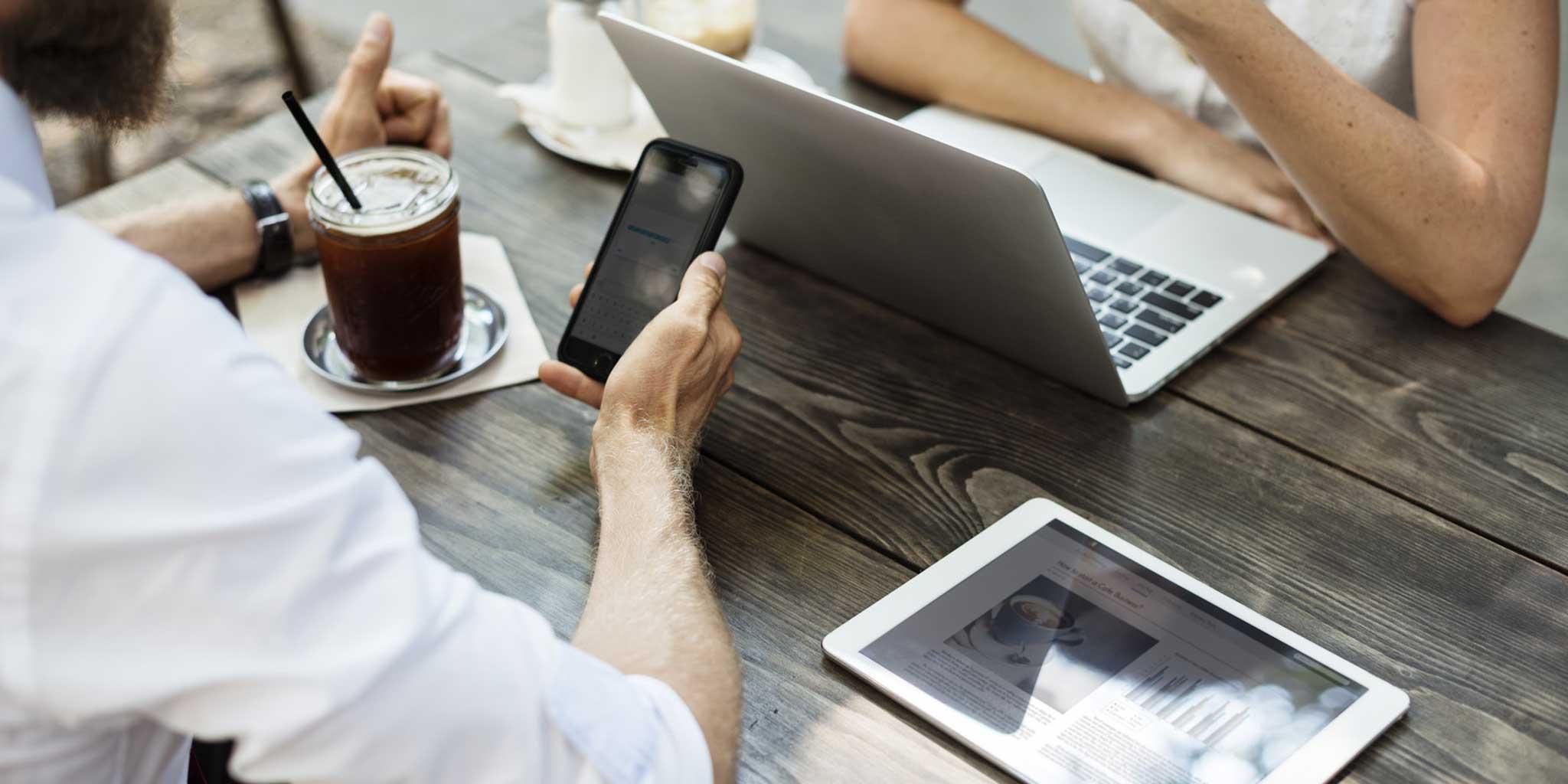 Mensen aan tafel met een tablet, smartphone, laptop en drank