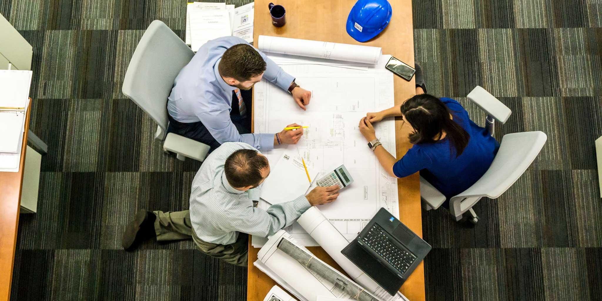 mannen en vrouw bezig aan een bouwplan op een bureau