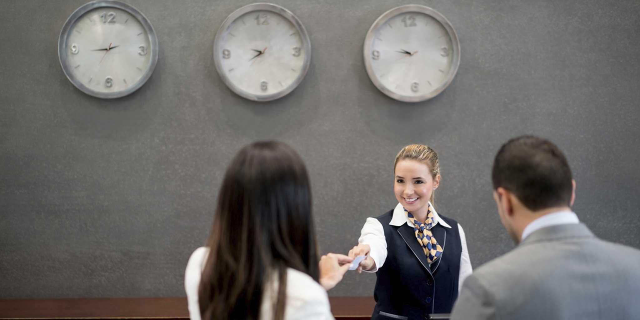 Vrouw aan het onthaal geeft een kaart aan een andere vrouw