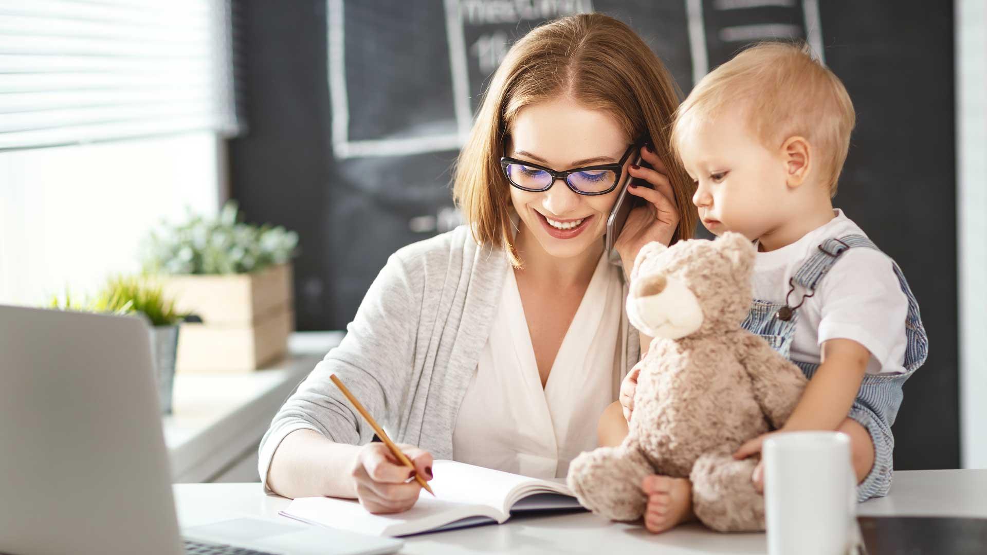 Thuiswerk- een vrouw bellend aan tafel terwijl ze bezig is in een schrift. Een baby zit op tafel naast haar