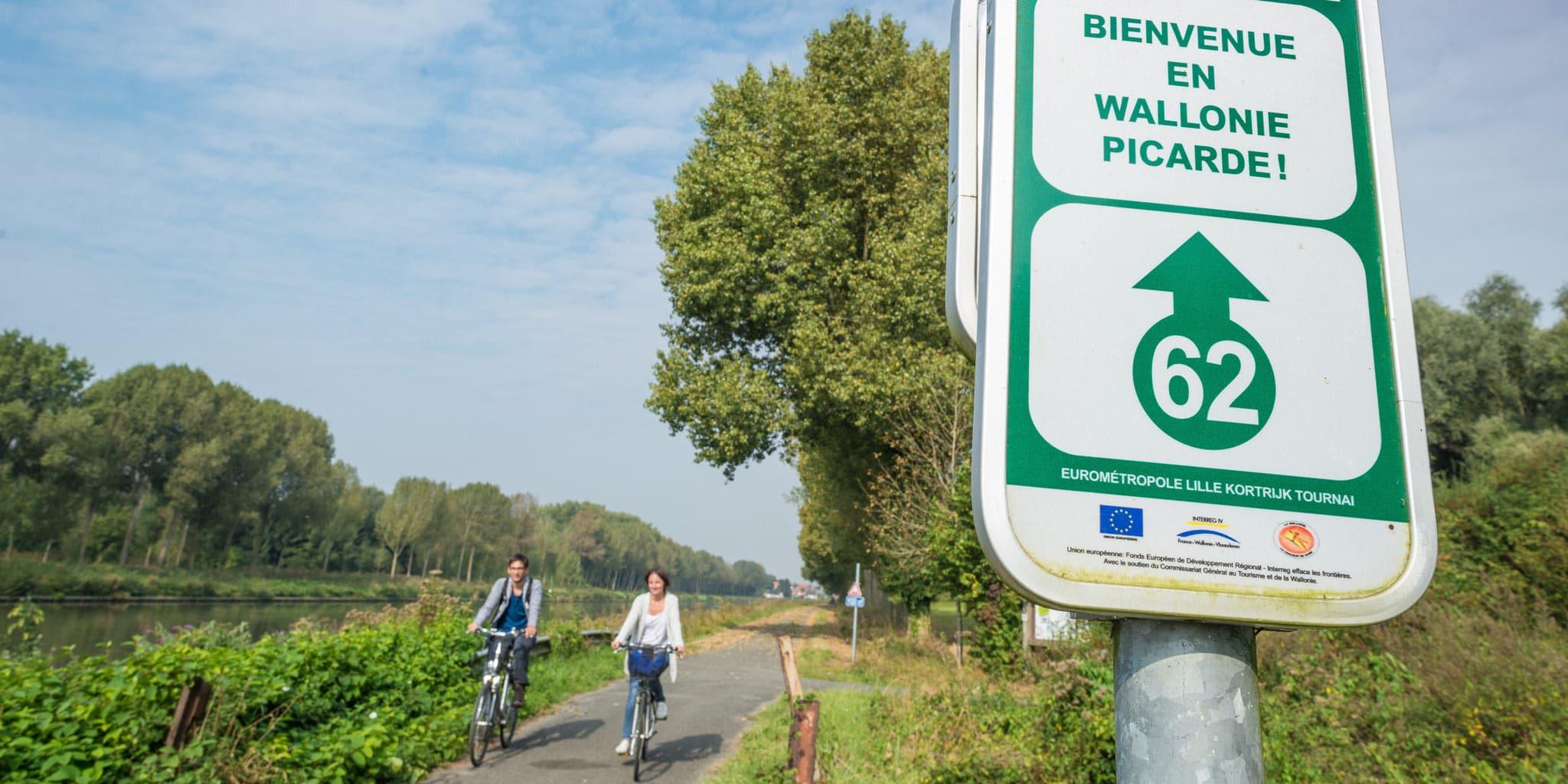 Bord verwelkoming Wallonië Picarde met op de achtergrond twee fietsers