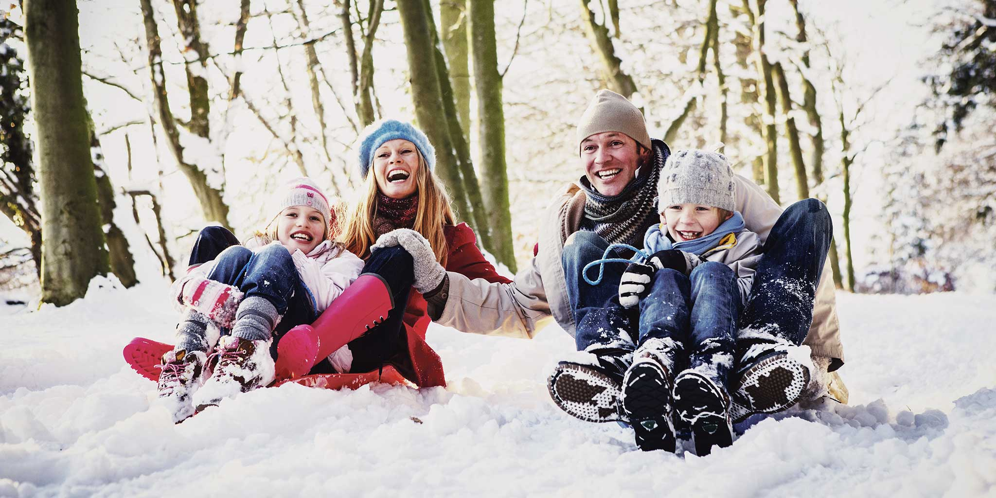 gezin lachend in de sneeuw