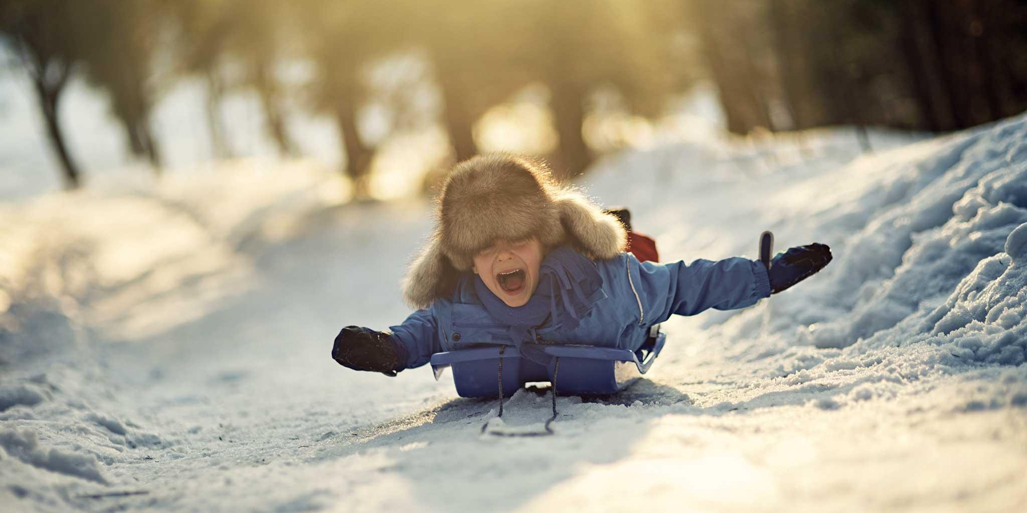 Kleine kind op een slee in de sneeuw