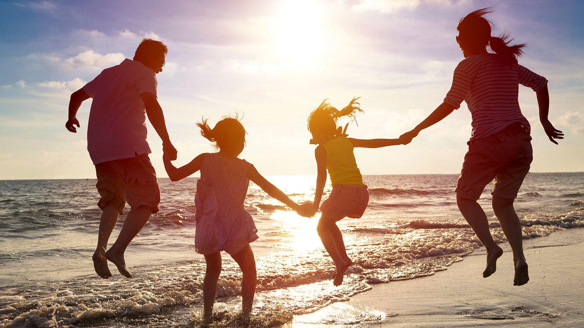 Gezin samen aan het springend op het strand