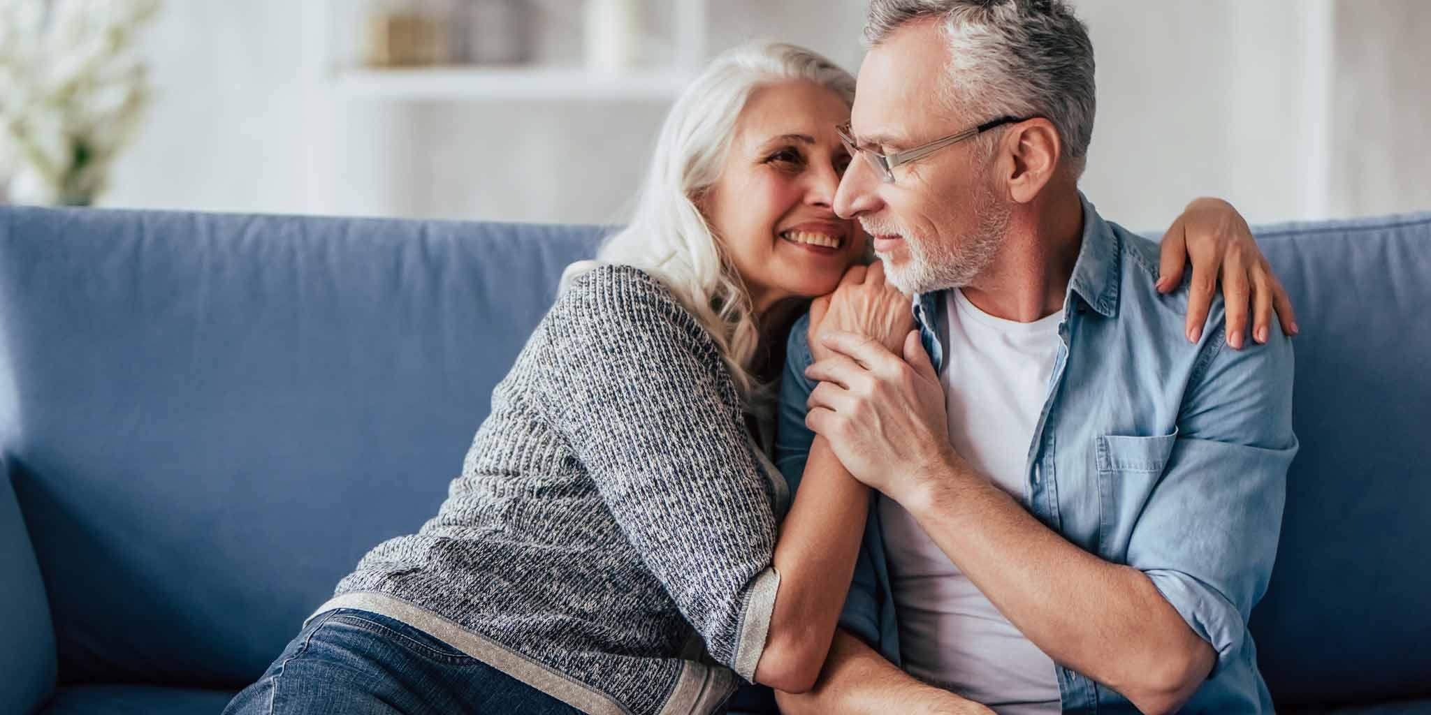 fokus50plus_energiezuinig- vrouw omhelst man in een blauwe zetel