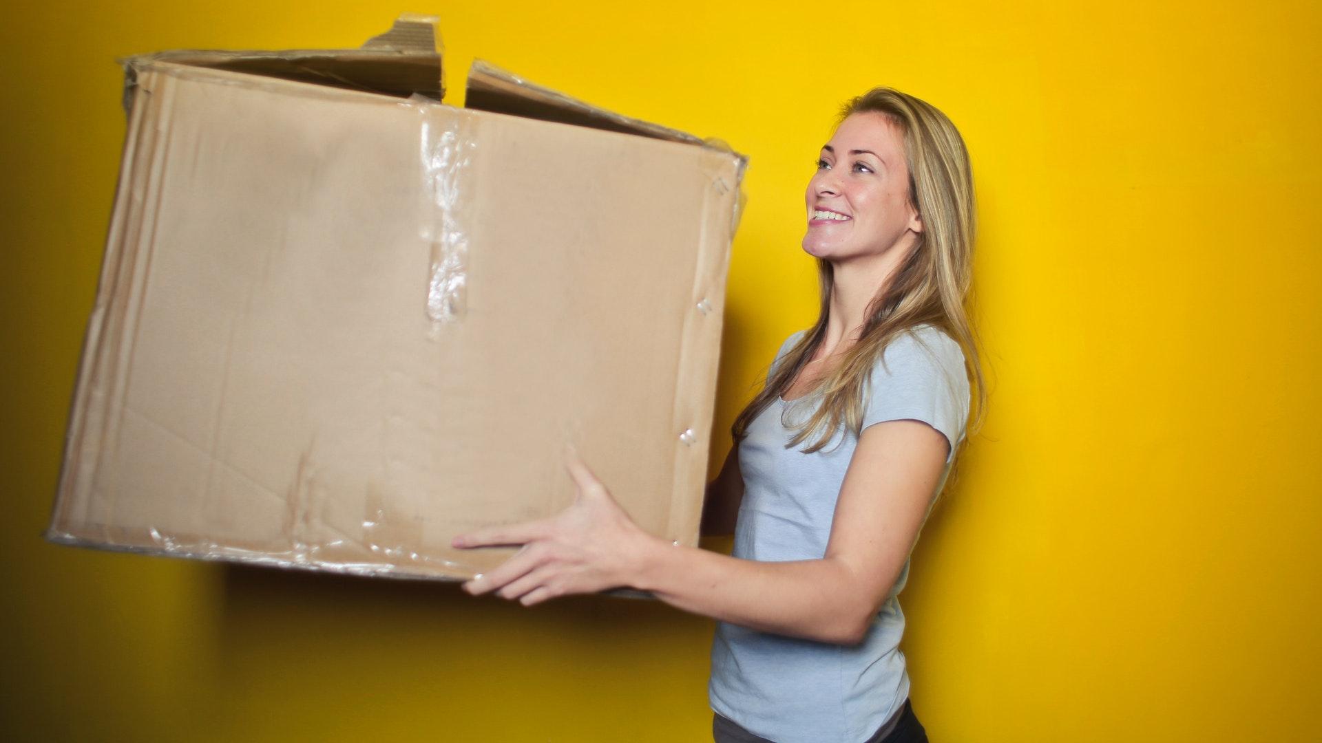 une fille qui déménage en utilisant une boîte de déménagement